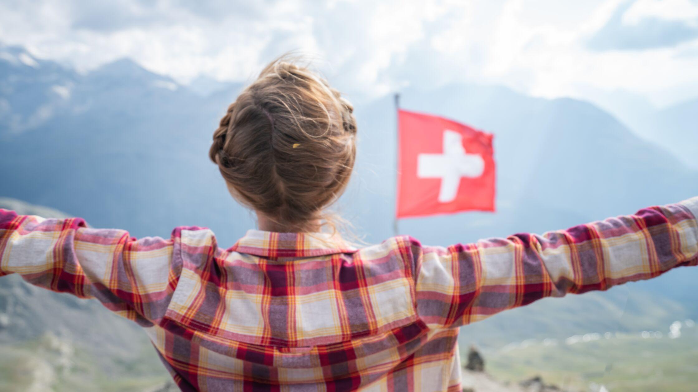 Frau am Matterhorn mit Schweizer Flagge