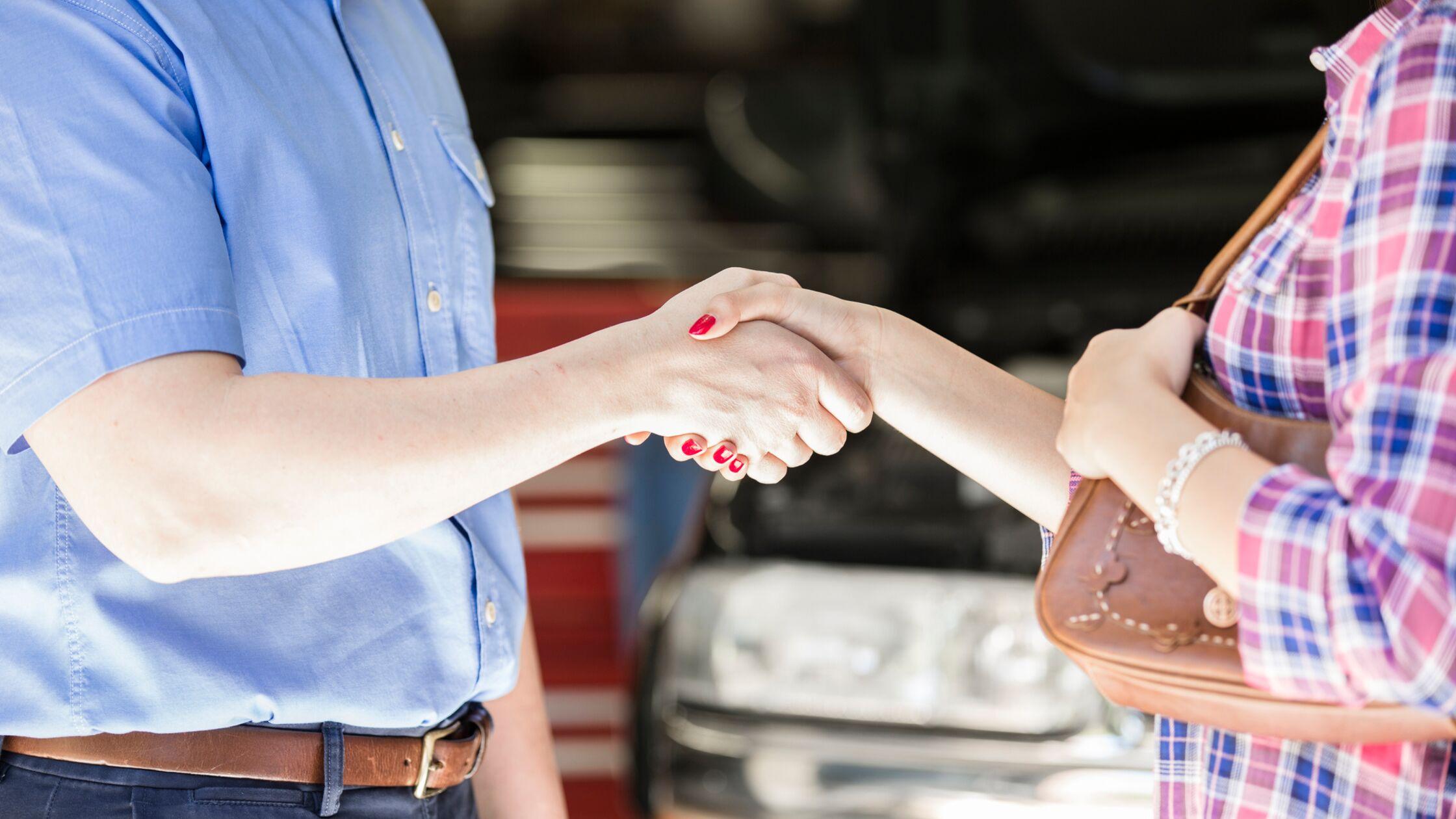 Zwei Personen schütteln Hände, im Hintergrund ein Auto
