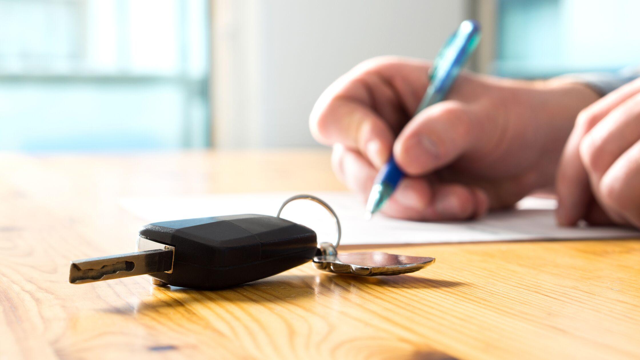 Hand mit Stift und Autoschlüssel unterschreibt einen Vertrag