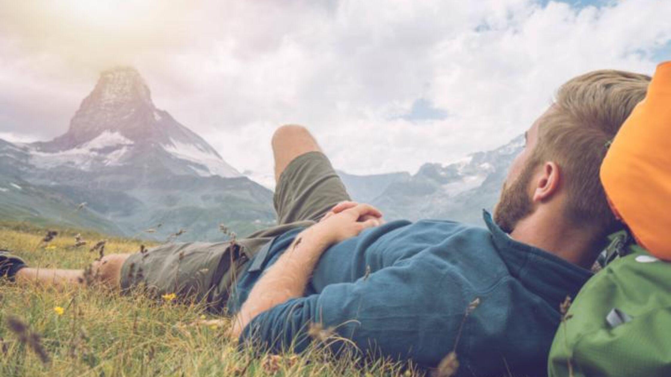 Wanderer liegt auf Bergwiese und schaut aufs Matterhorn