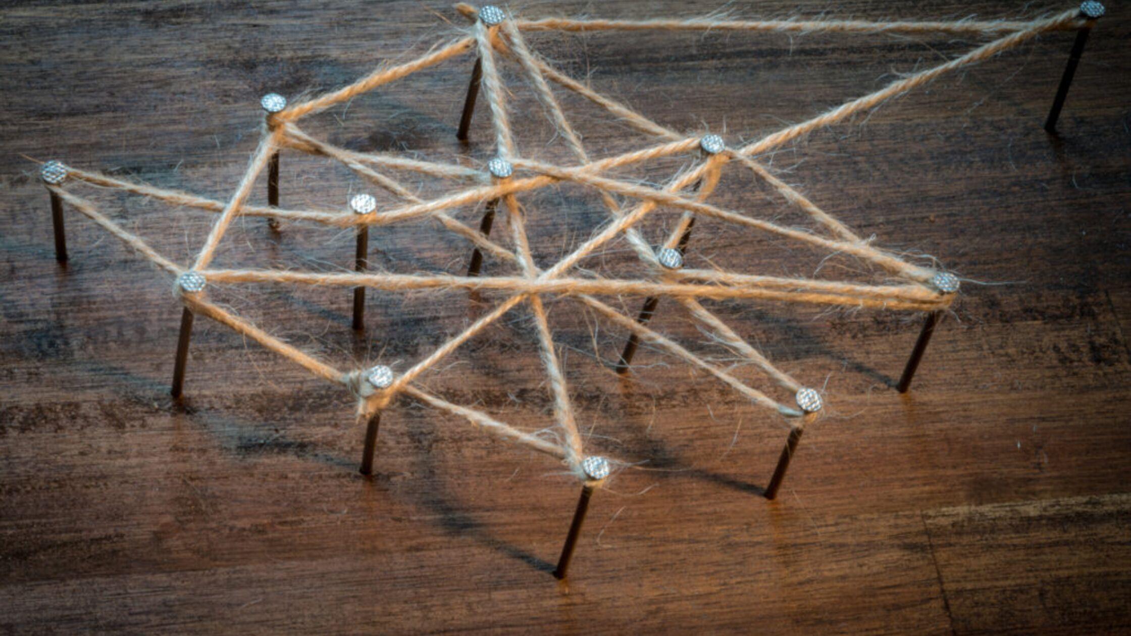 Nägel und Schnüre symbolisieren Vernetzung