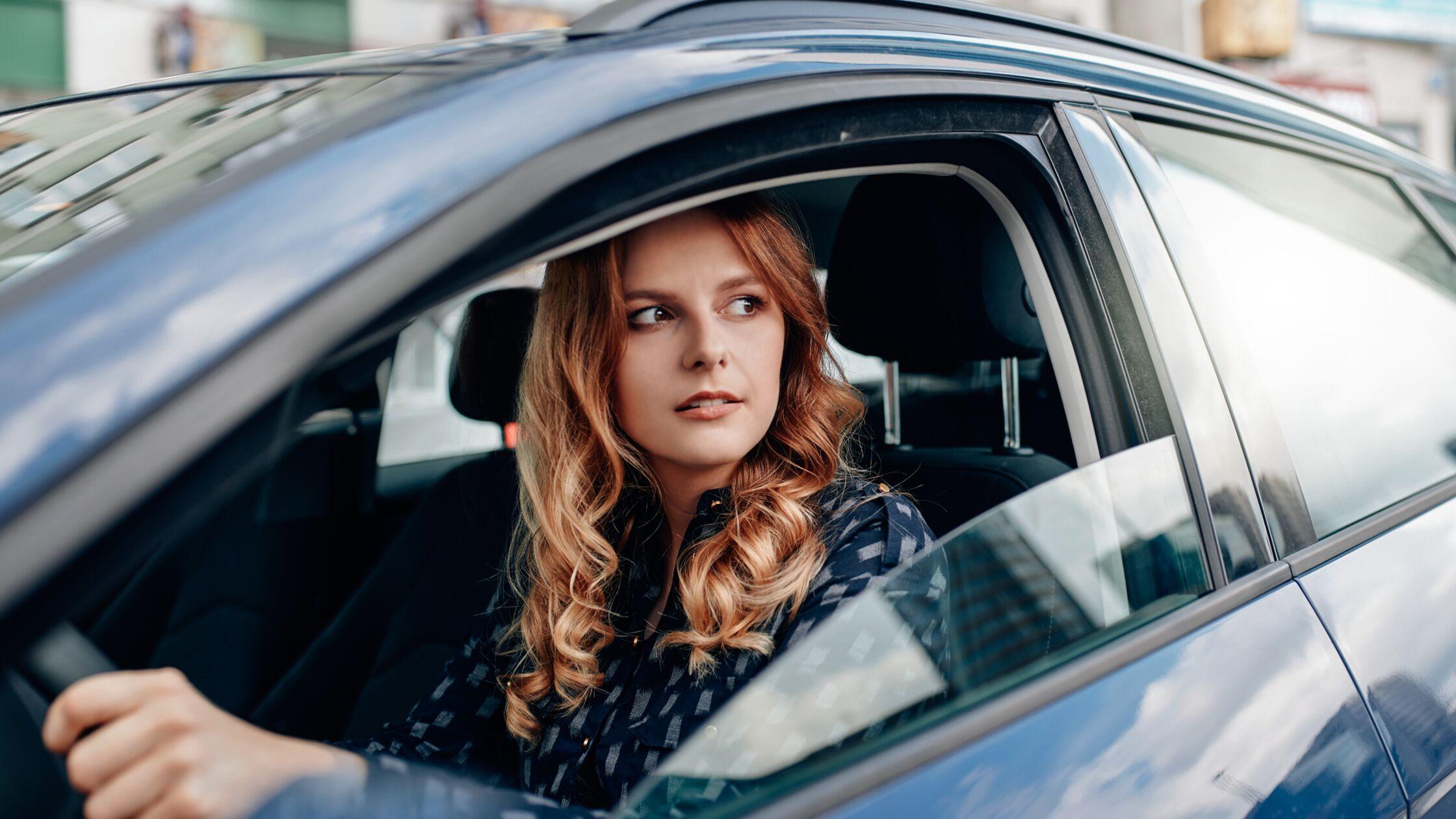Junge Frau am Steuer eines Autos schaut aus dem Fenster