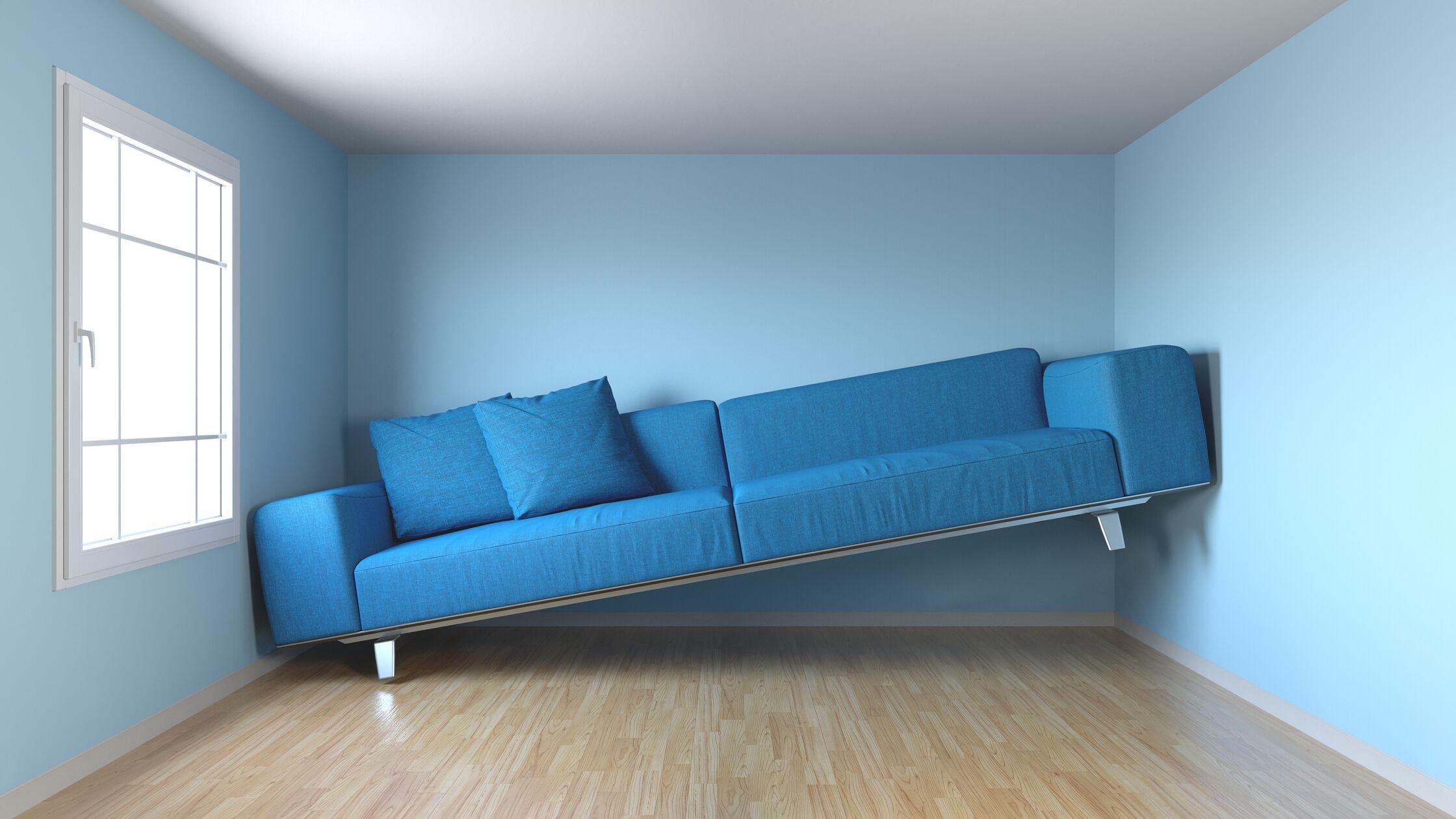 Ein blaues Sofa klemmt mit dem rechten Ende an der Wand, weil es nicht in den Raum passt