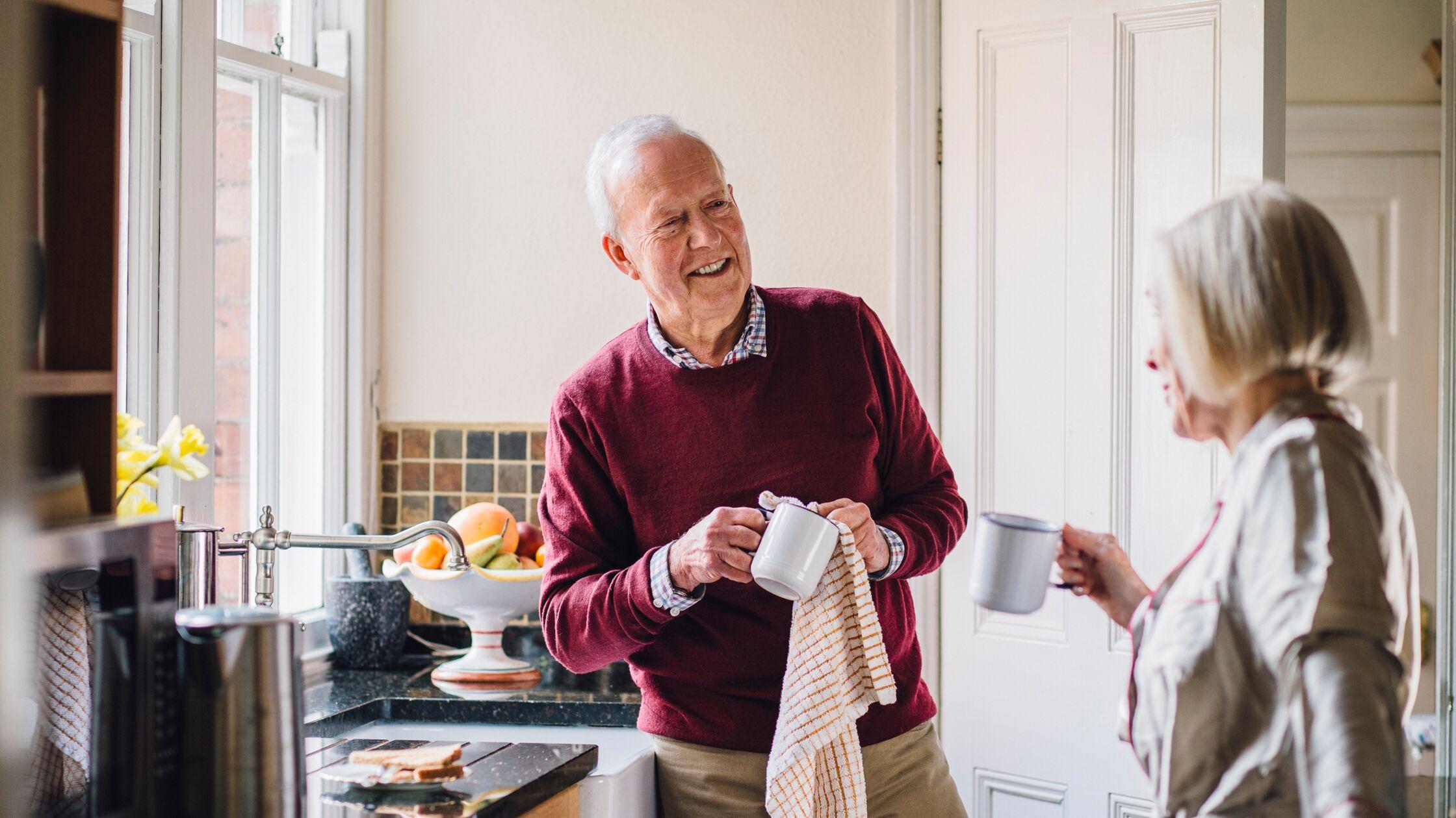 Älterer Mann trocknet Kaffeebecher mit kariertem Geschirrtuch ab