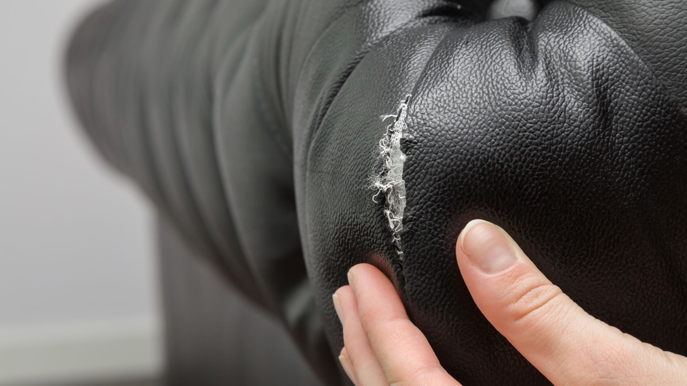 Hand deutet auf Riss an einem schwarzen Ledersofa