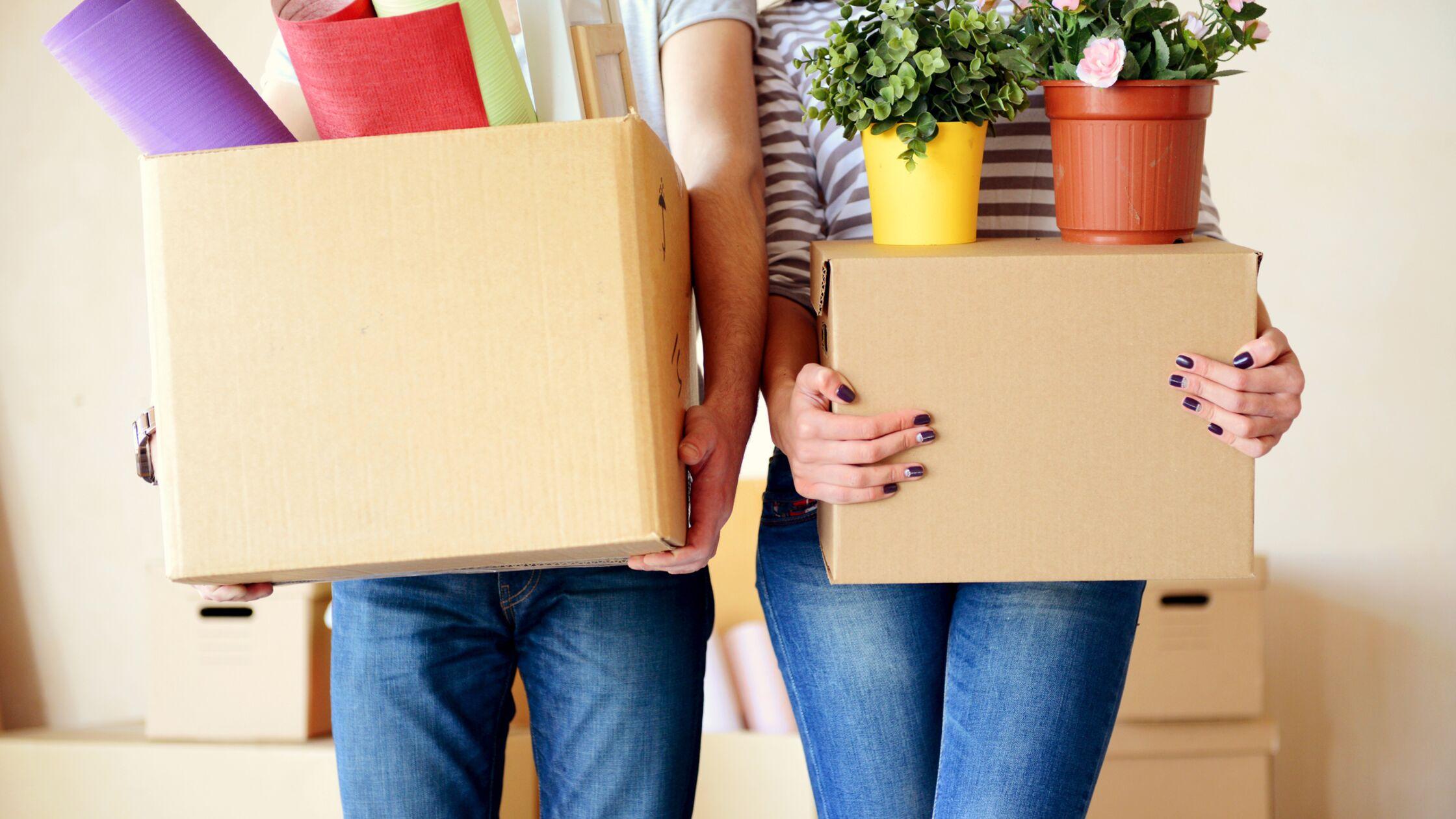 Paar steht mit gepackten Umzugskartons im Wohnzimmer