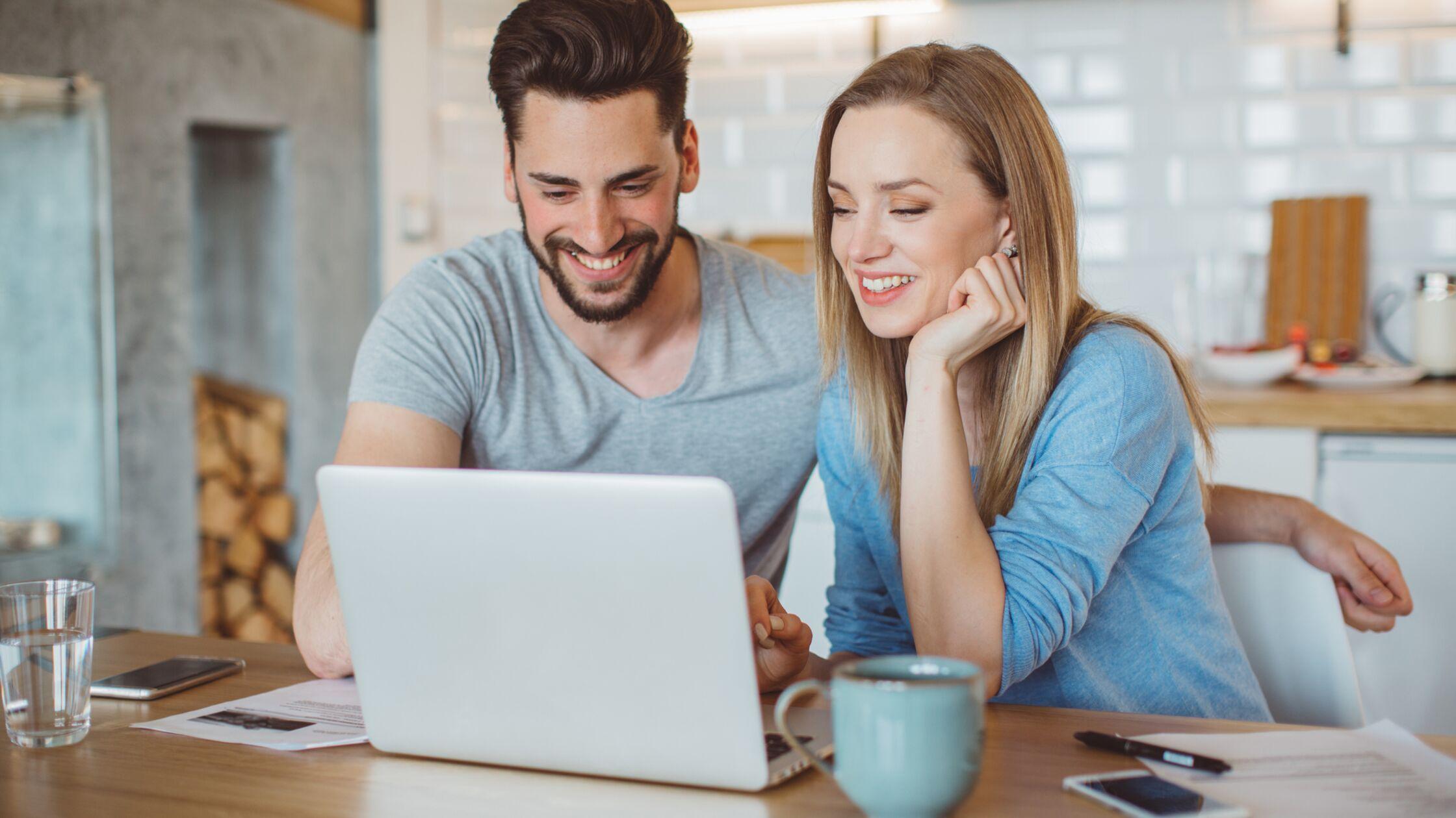 Junges Paar sitzt am Laptop und begleicht Rechnung