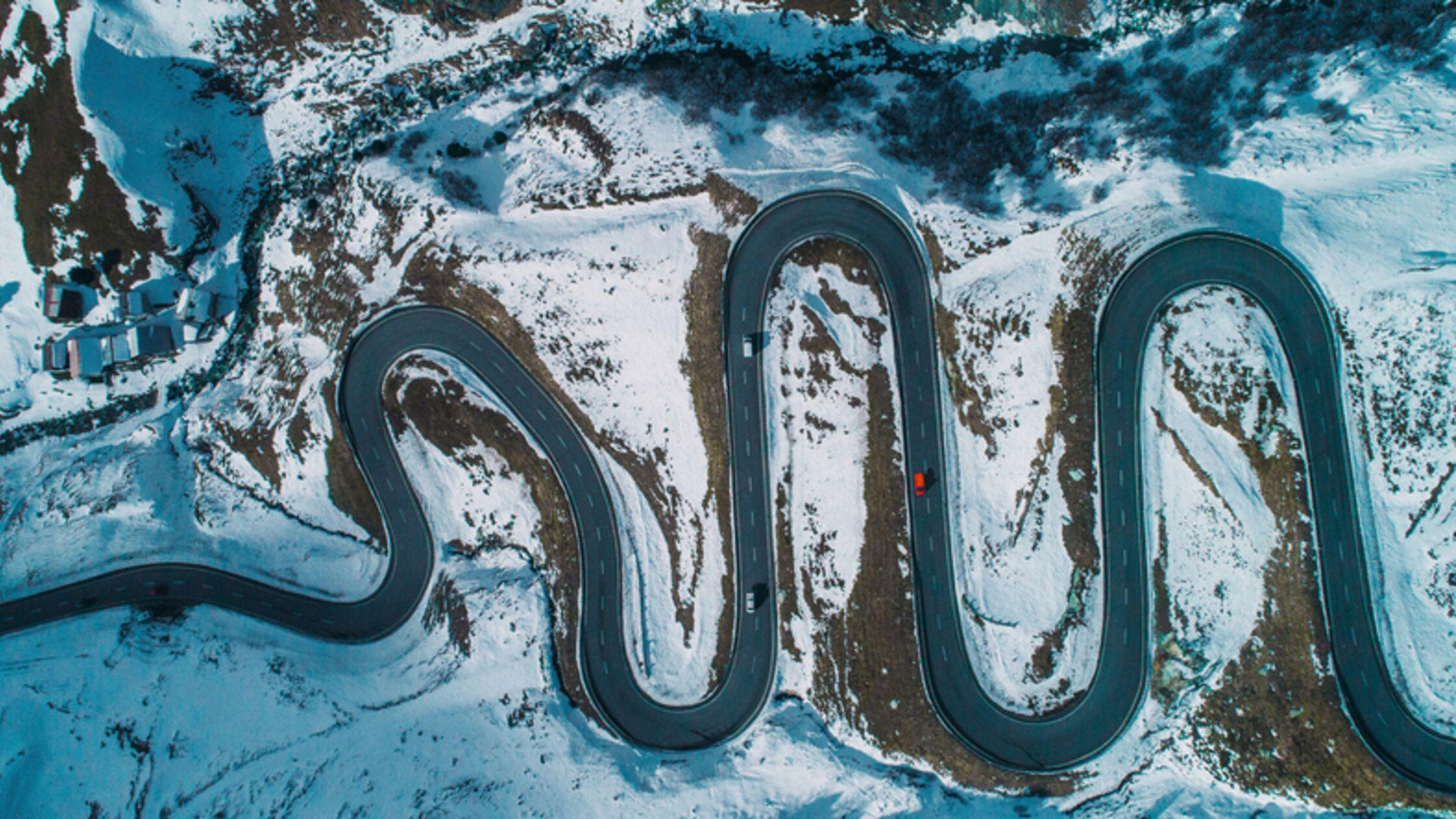verschneite Serpentinenstaße in der Schweiz