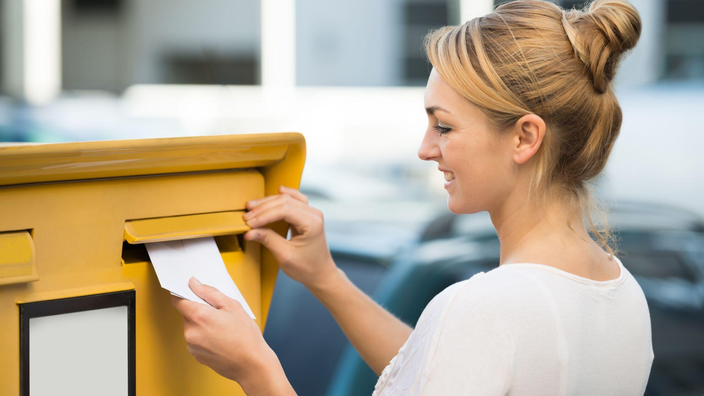 Junge Frau steckt einen Brief in den Postkasten.