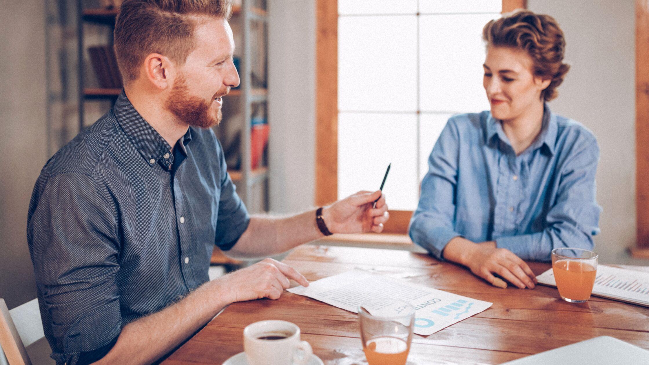 Mann überreicht Frau einen Stift zum unterschreiben eines Dokuments.
