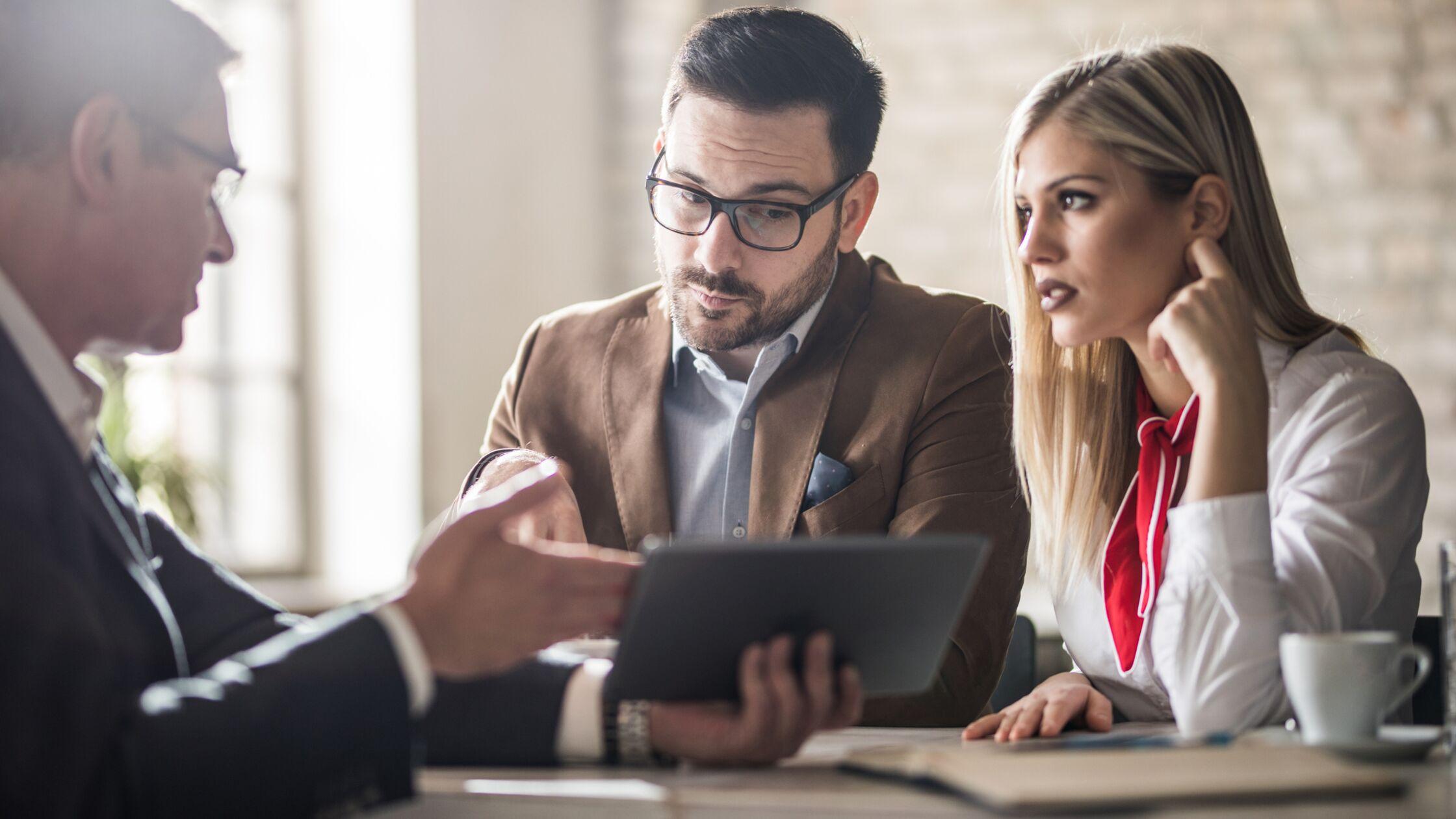 Junges Paar schaut skeptisch auf das Tablet, das ein Mann im Anzug hält