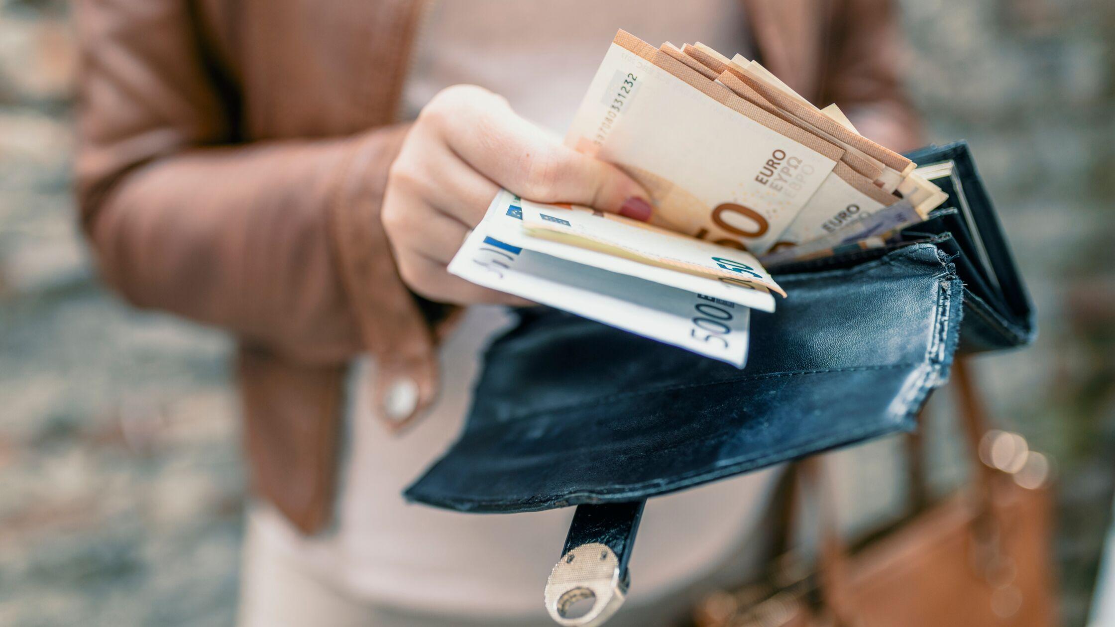 Frauenhand nimmt ein Bündel Geldscheine aus einem Geldbeutel