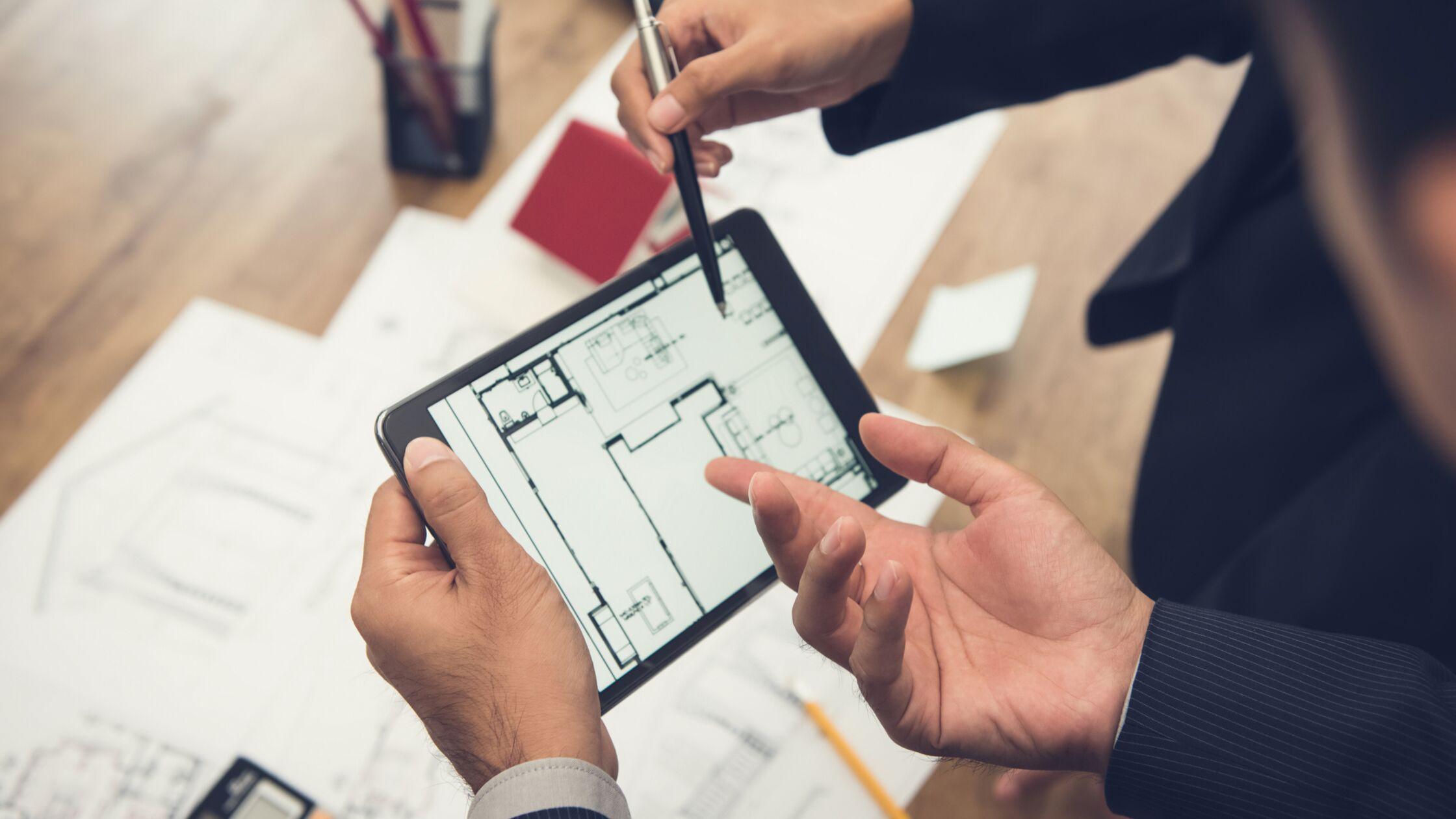 Finger zeigen auf Wohnungsgrundriss am Tablet