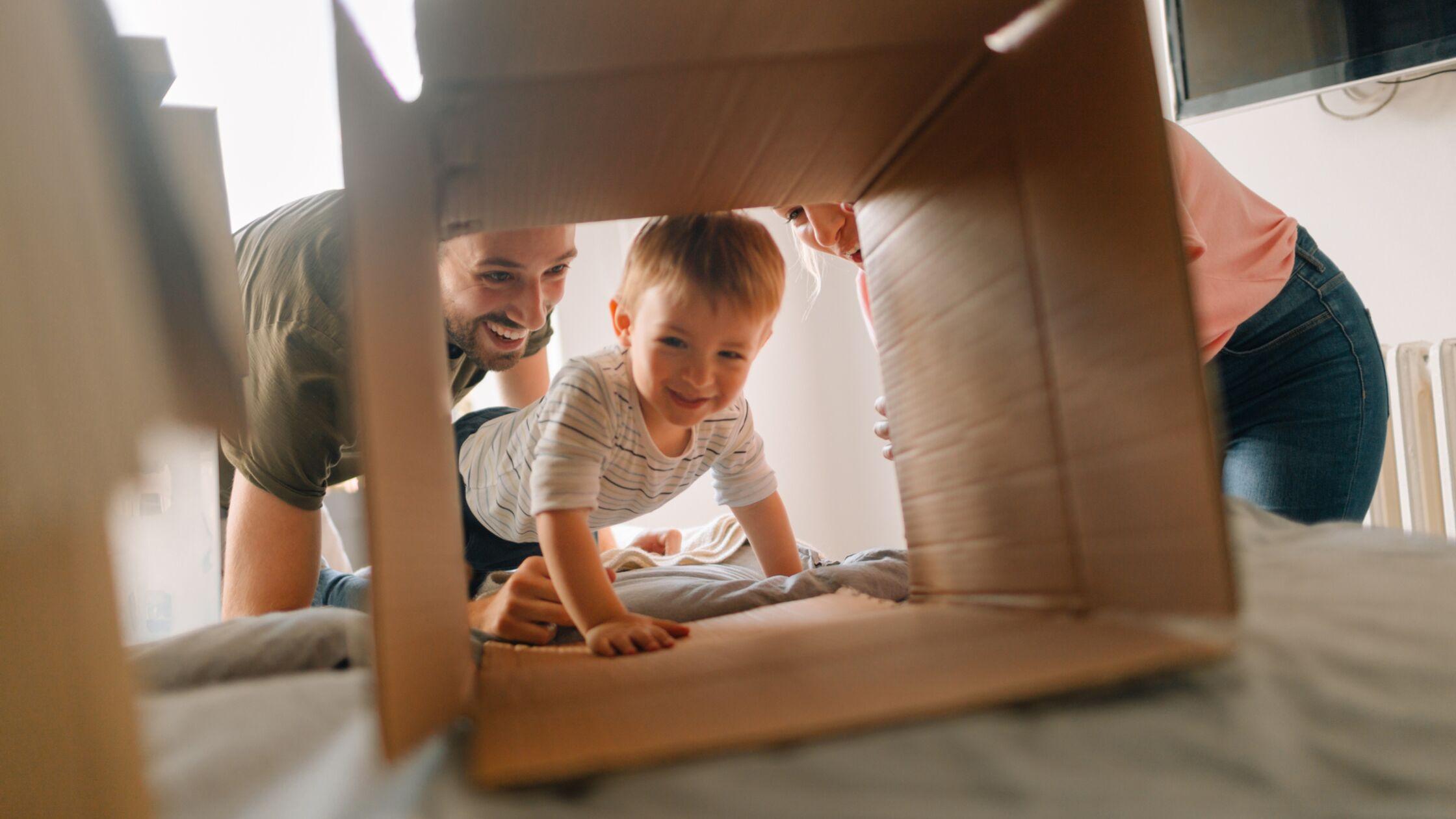 Lachende Familie mit Kleinkind, das in einen Umzugskarton krabbelt