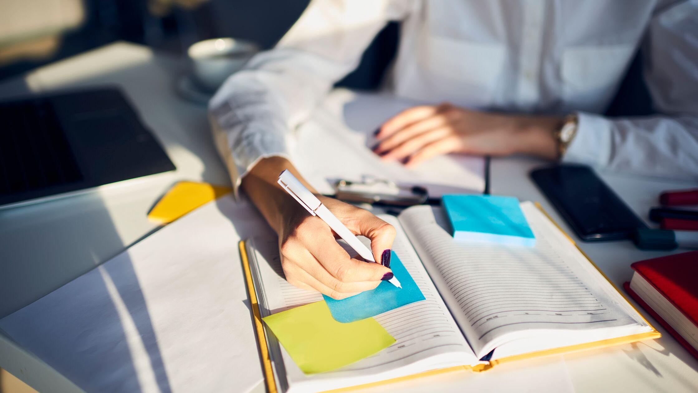 Frau schreibt in ein Notizbuch voller Notizzettel