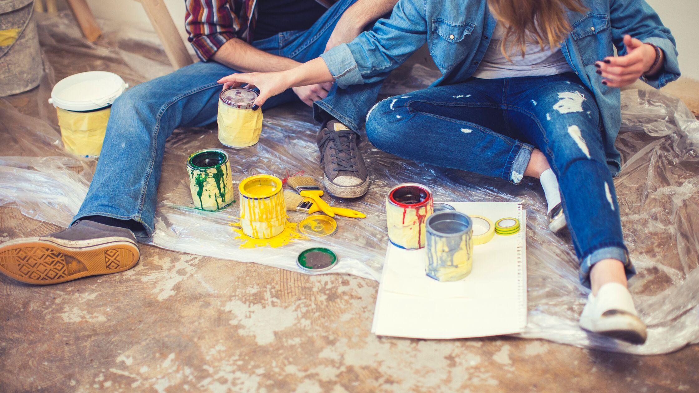 Junges Paar sitzt auf dem Boden zwischen leeren Farbeimern und Farbdosen