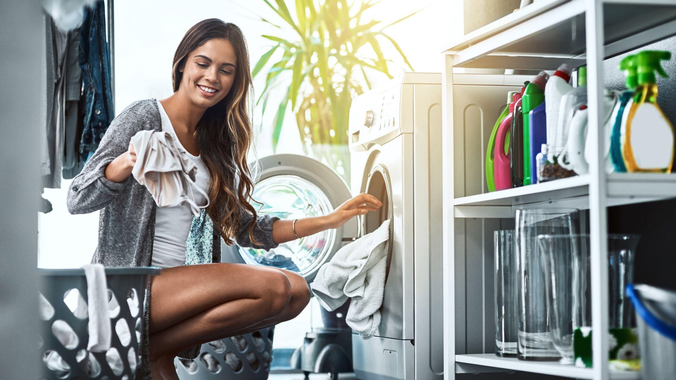 Junge Frau wäscht Wäsche in ihrer neuen Wohnung