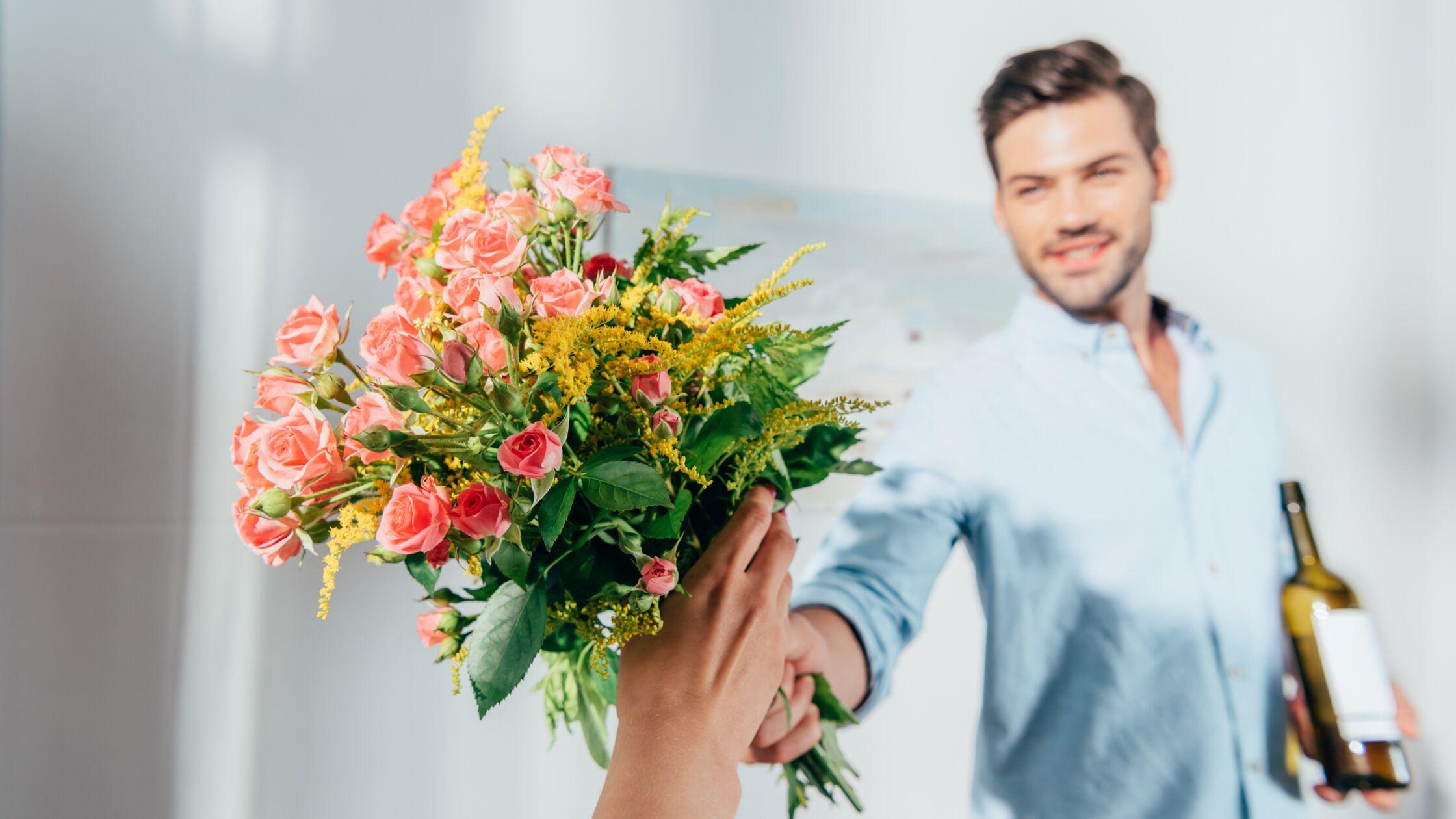 Junger Mann überreicht Frau Blumen und Wein.