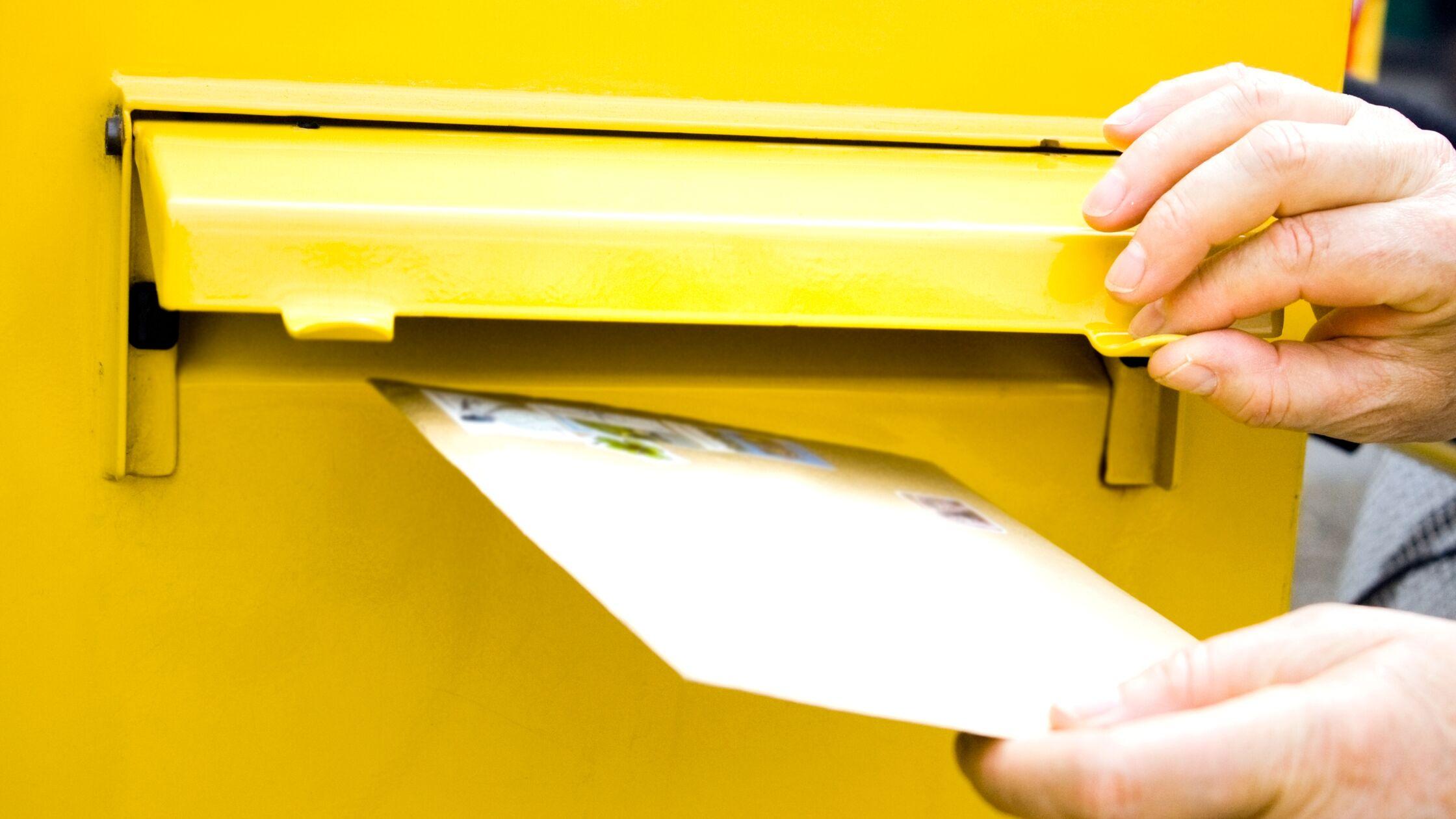 Brief wird in Briefkasten geschmissen