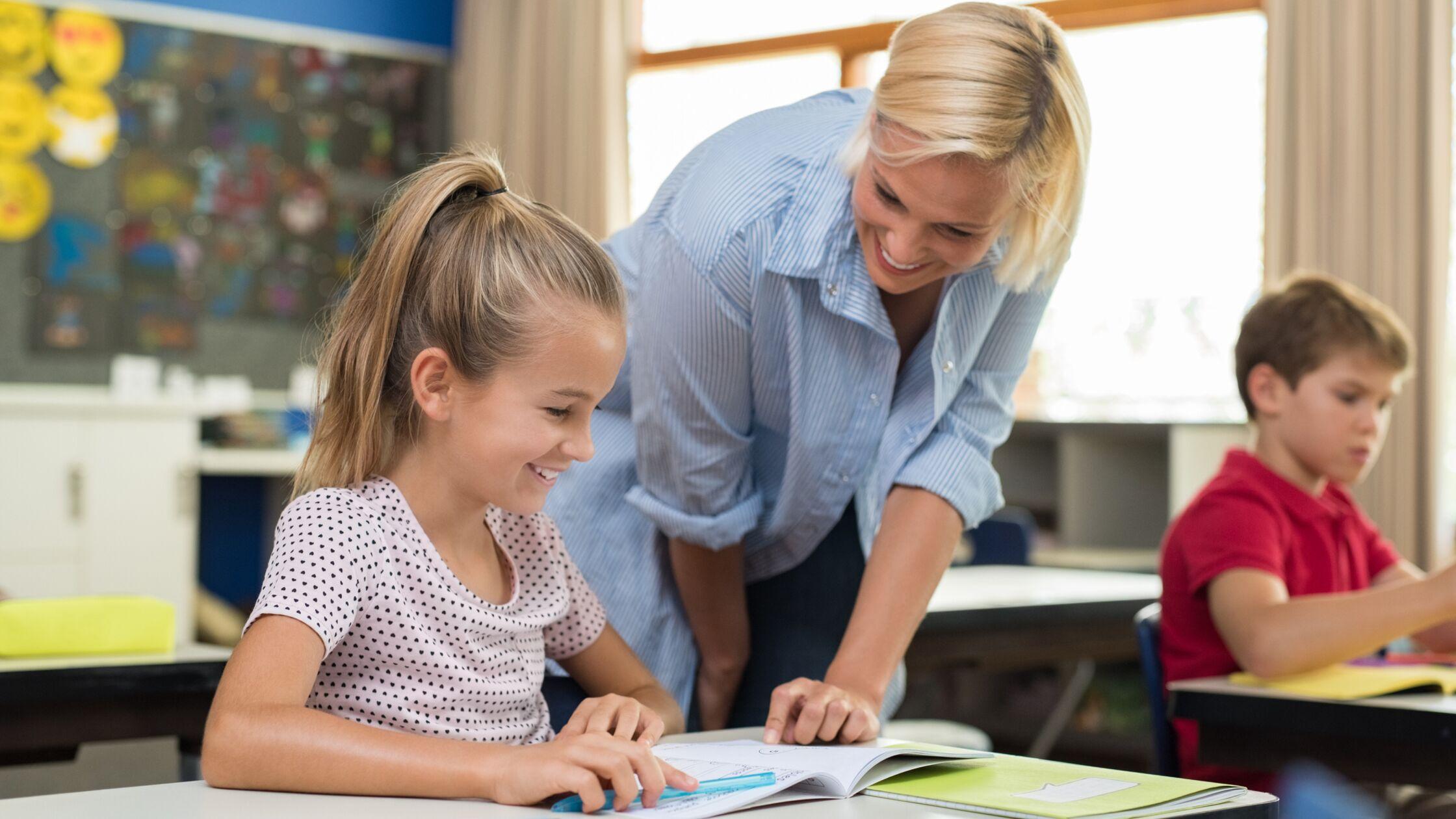 Lehrerin erklärt Schülerin Aufgabe aus dem Lehrplan im Bundesland