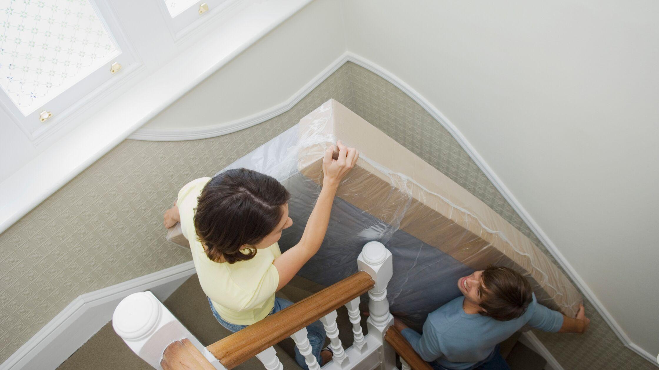 Paar trägt Matratze die Treppe runter