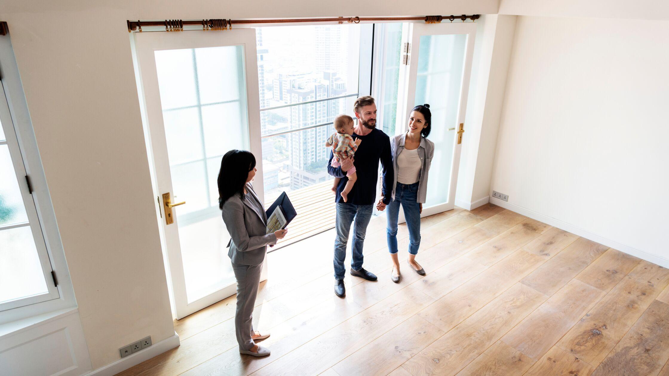 Drei Erwachsene und ein Baby in einer leeren Wohnung
