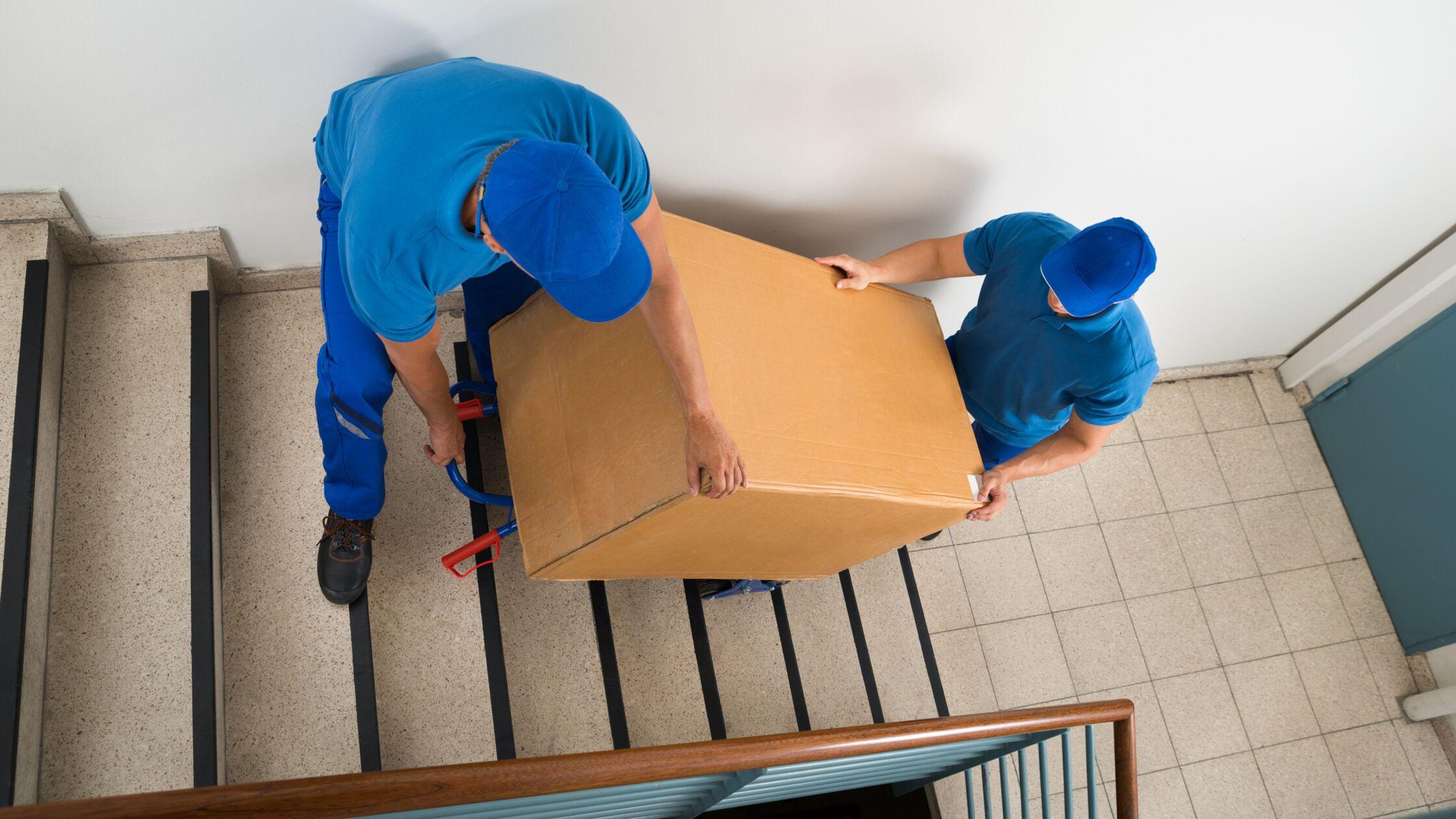 Zwei Männer transportieren Tresor auf Treppe