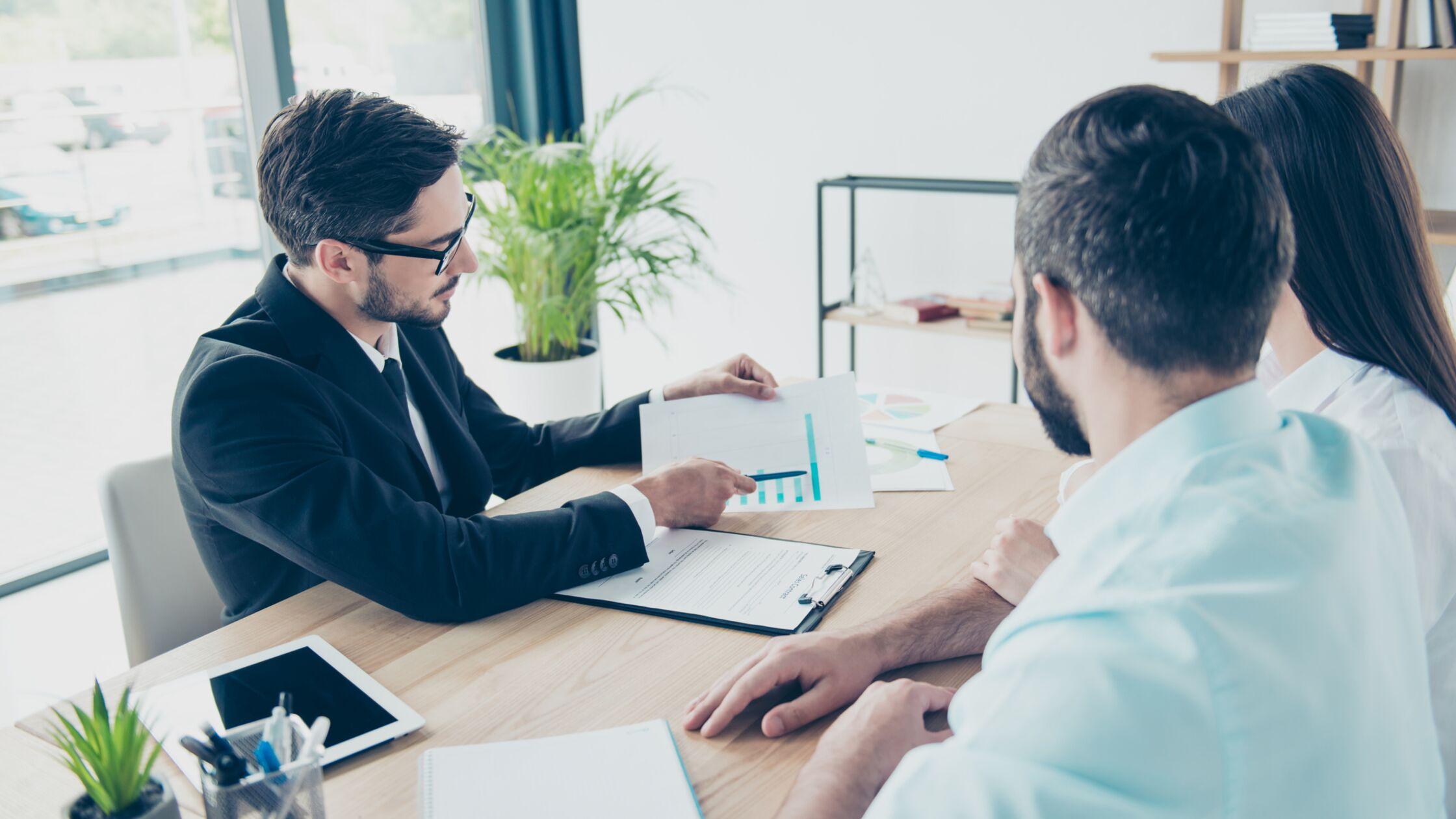 Drei Personen sitzen an einem Tisch und schauen auf ein Textdokument