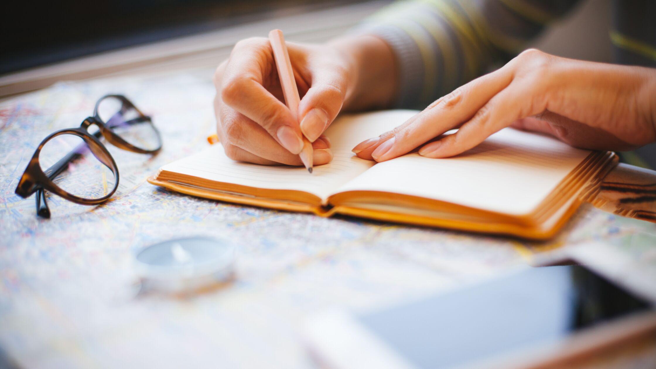 Hand schreibt etwas in ein Buch