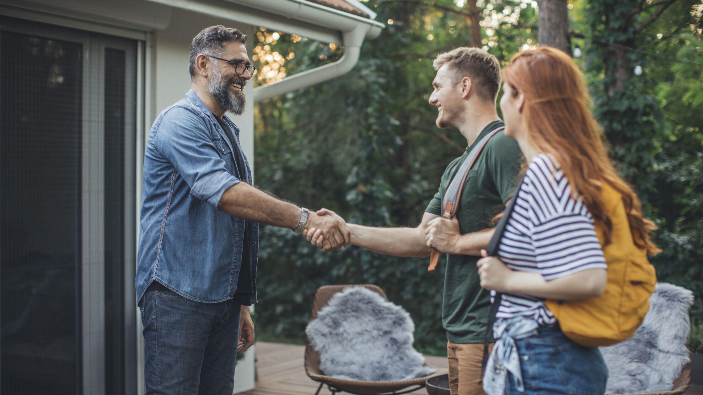 Ein Mann begrüßt ein Paar vor seinem Haus