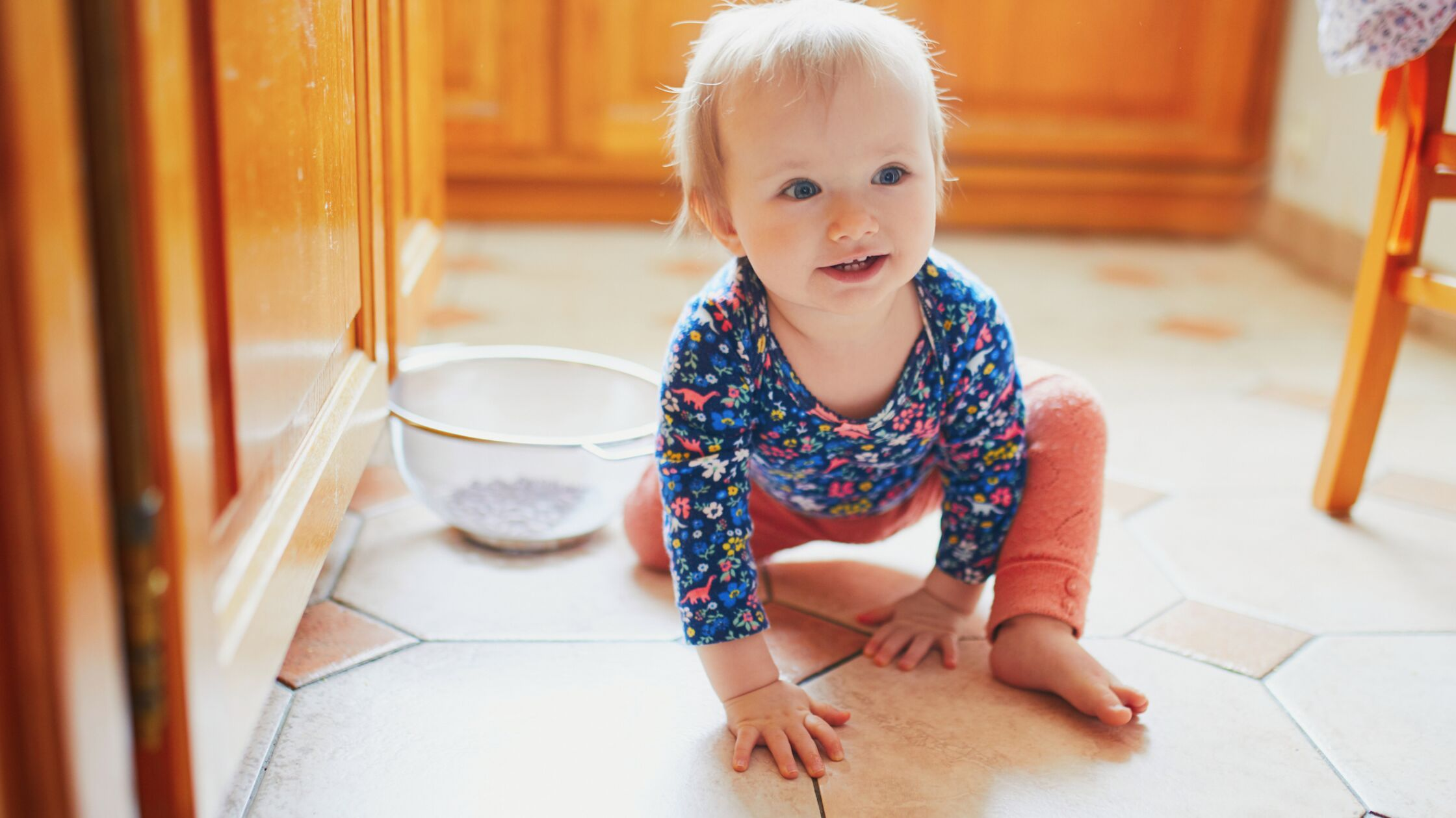 Kleinkind sitzt fröhlich auf dem Küchenfußboden.