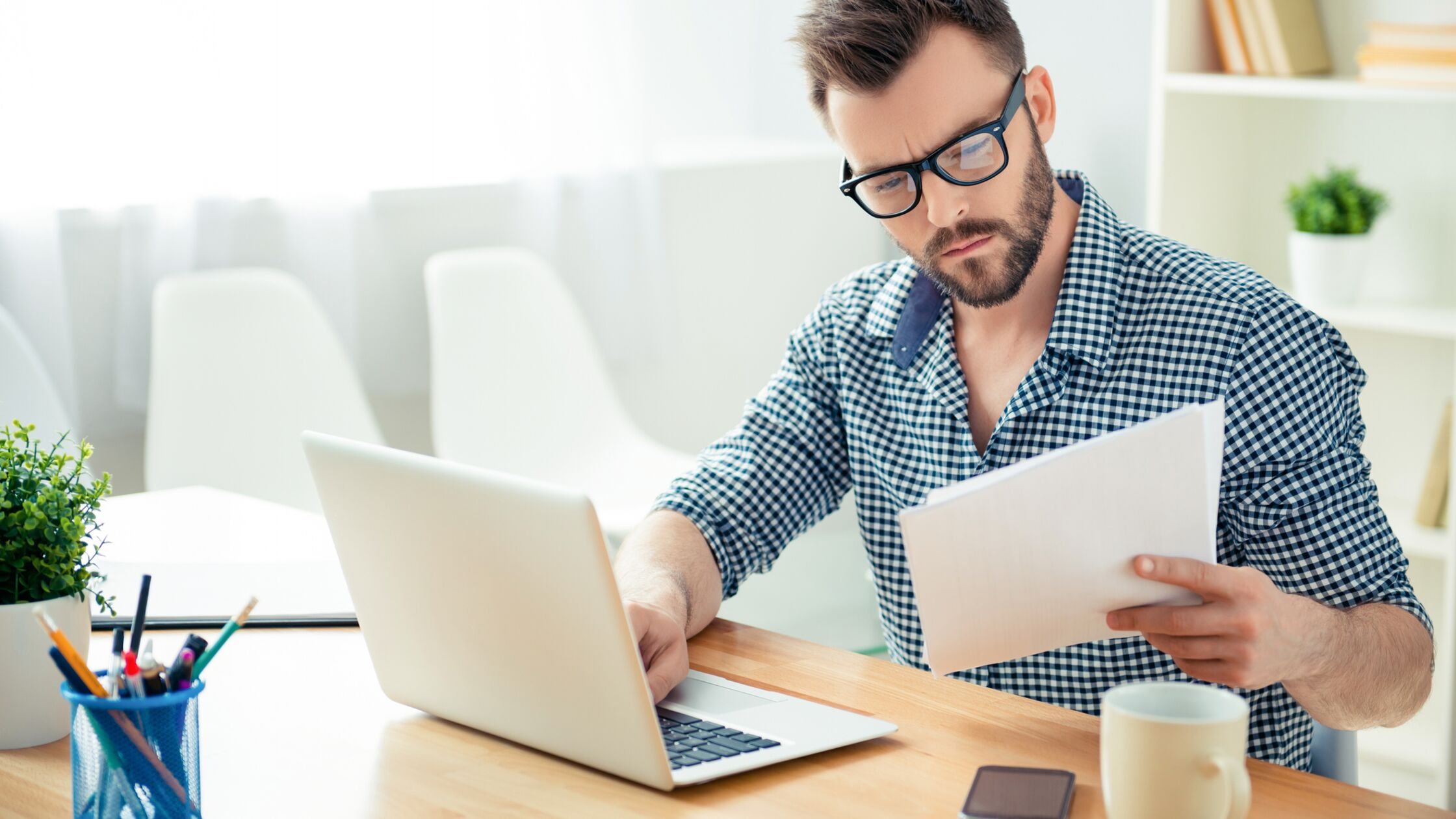 Mann sitzt vor Laptop und liest einen Brief