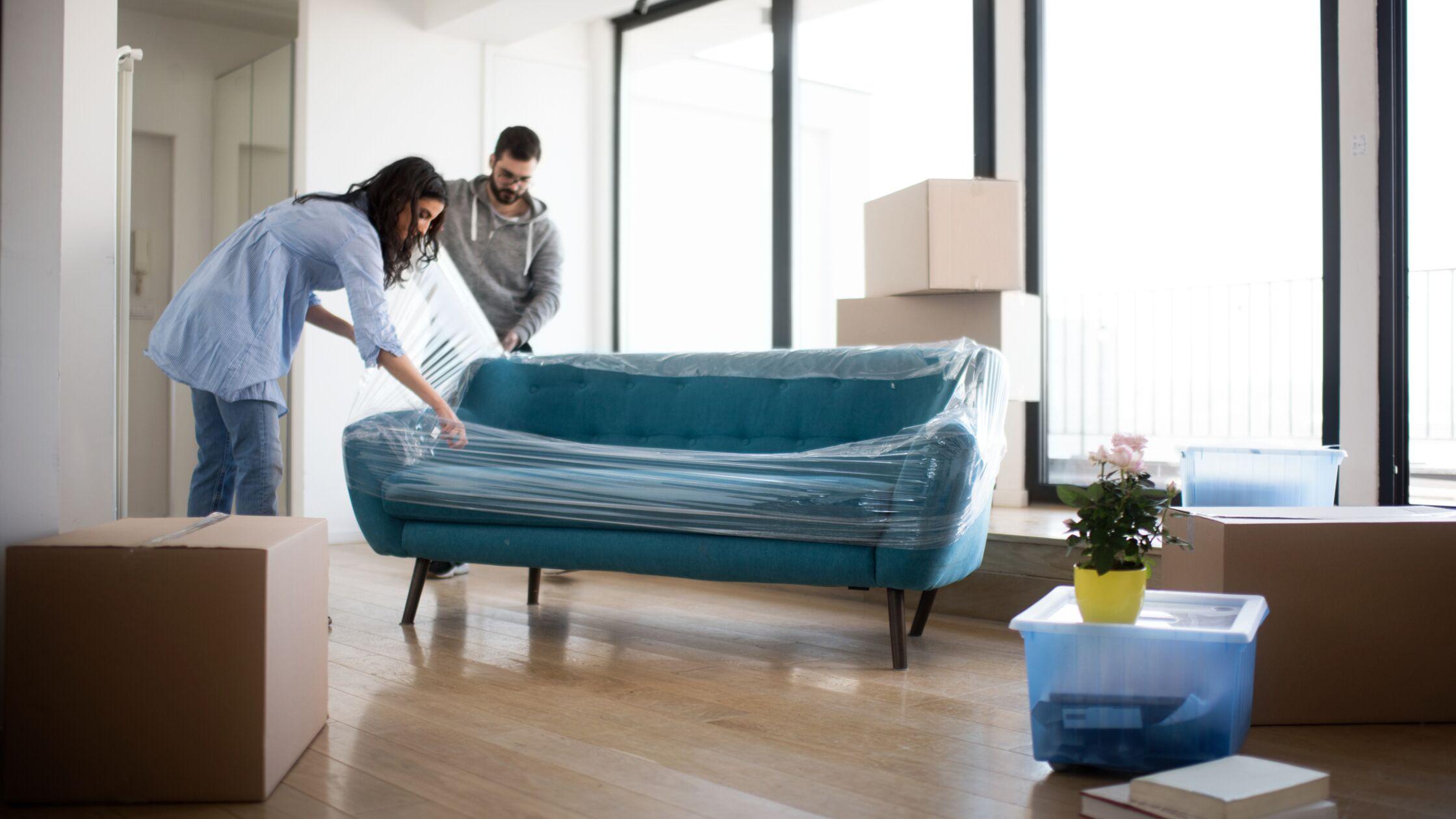 Paar packt Sofa in einer neuen Wohnung aus