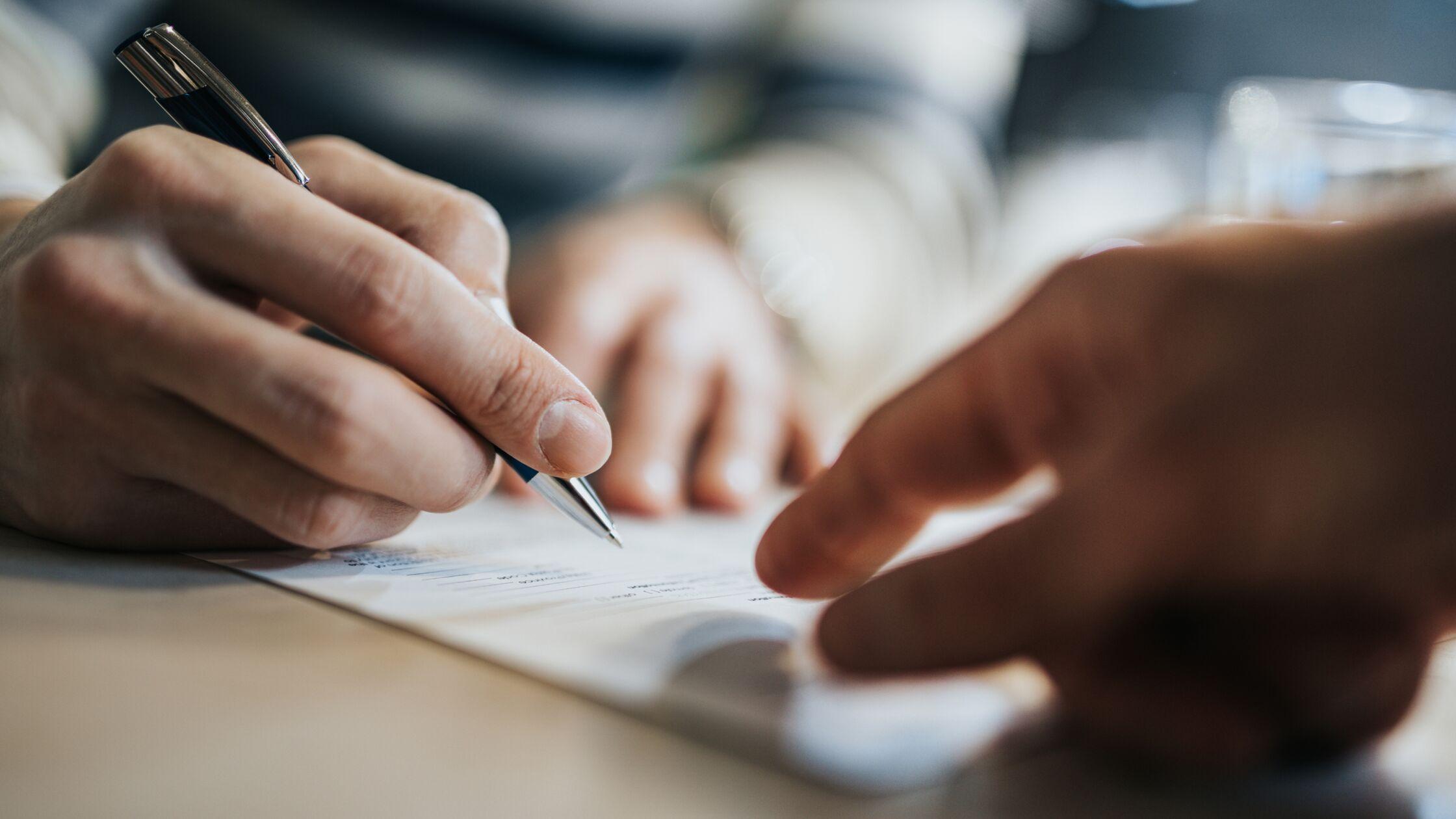 Hand unterschreibt Mietvertrag