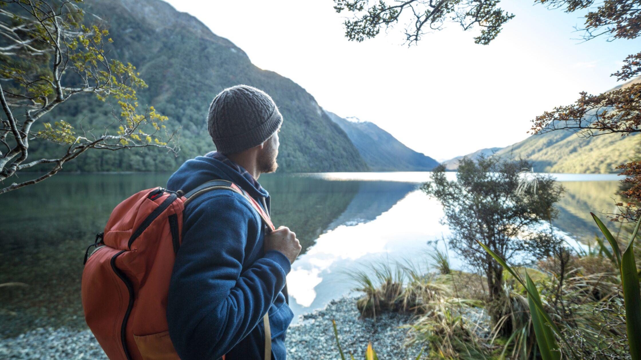 Mann schaut auf See in Neuseeland