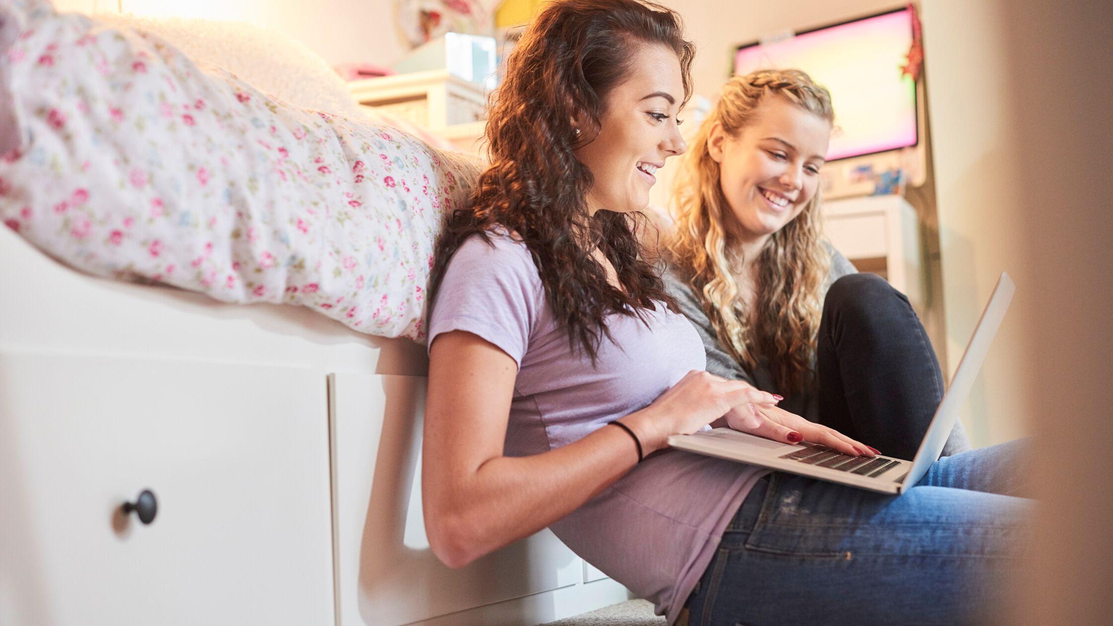 Zwei Frauen sitzen am Laptop vor dem Bett