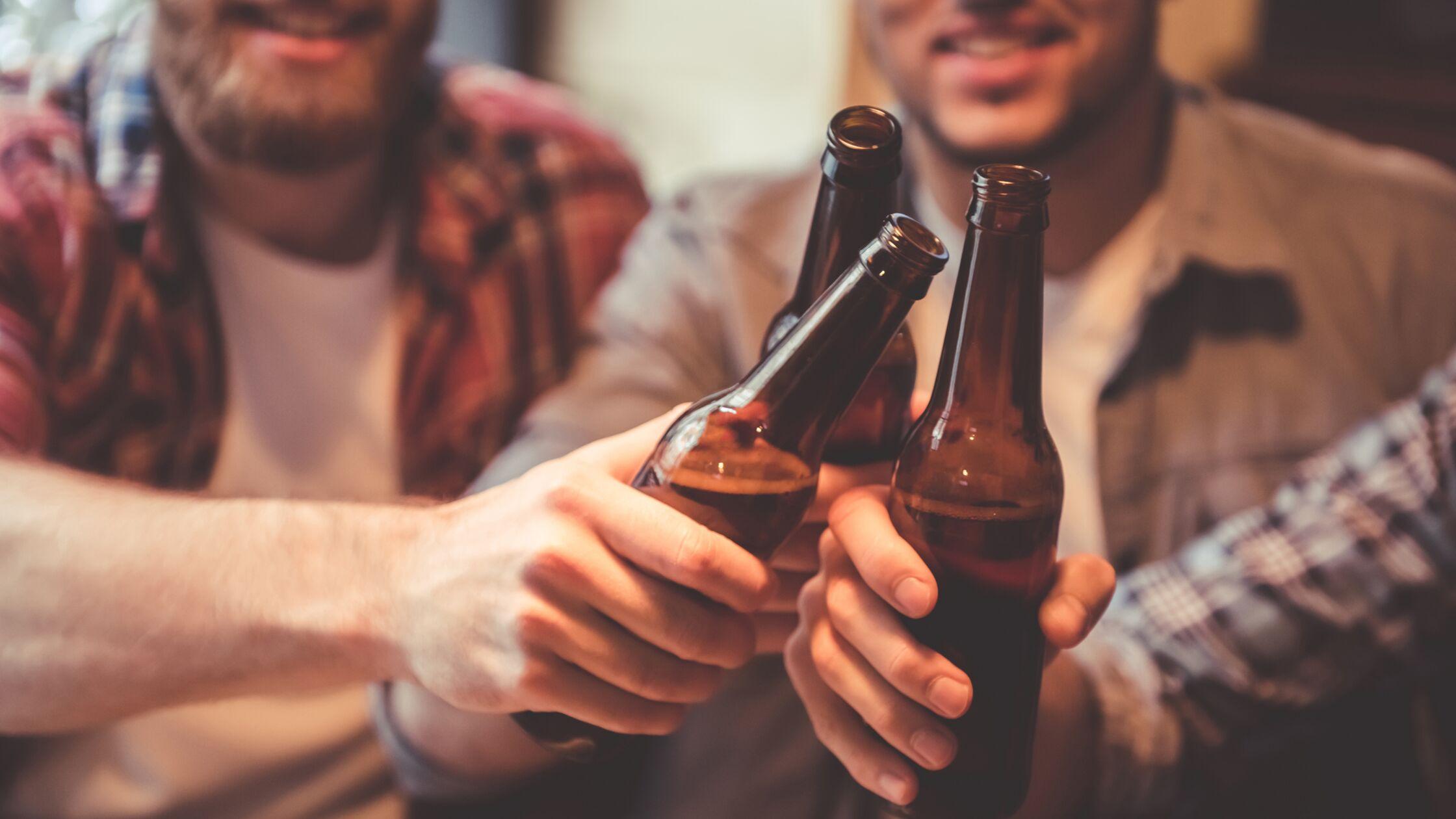 Männer stoßen mit Bierflaschen an