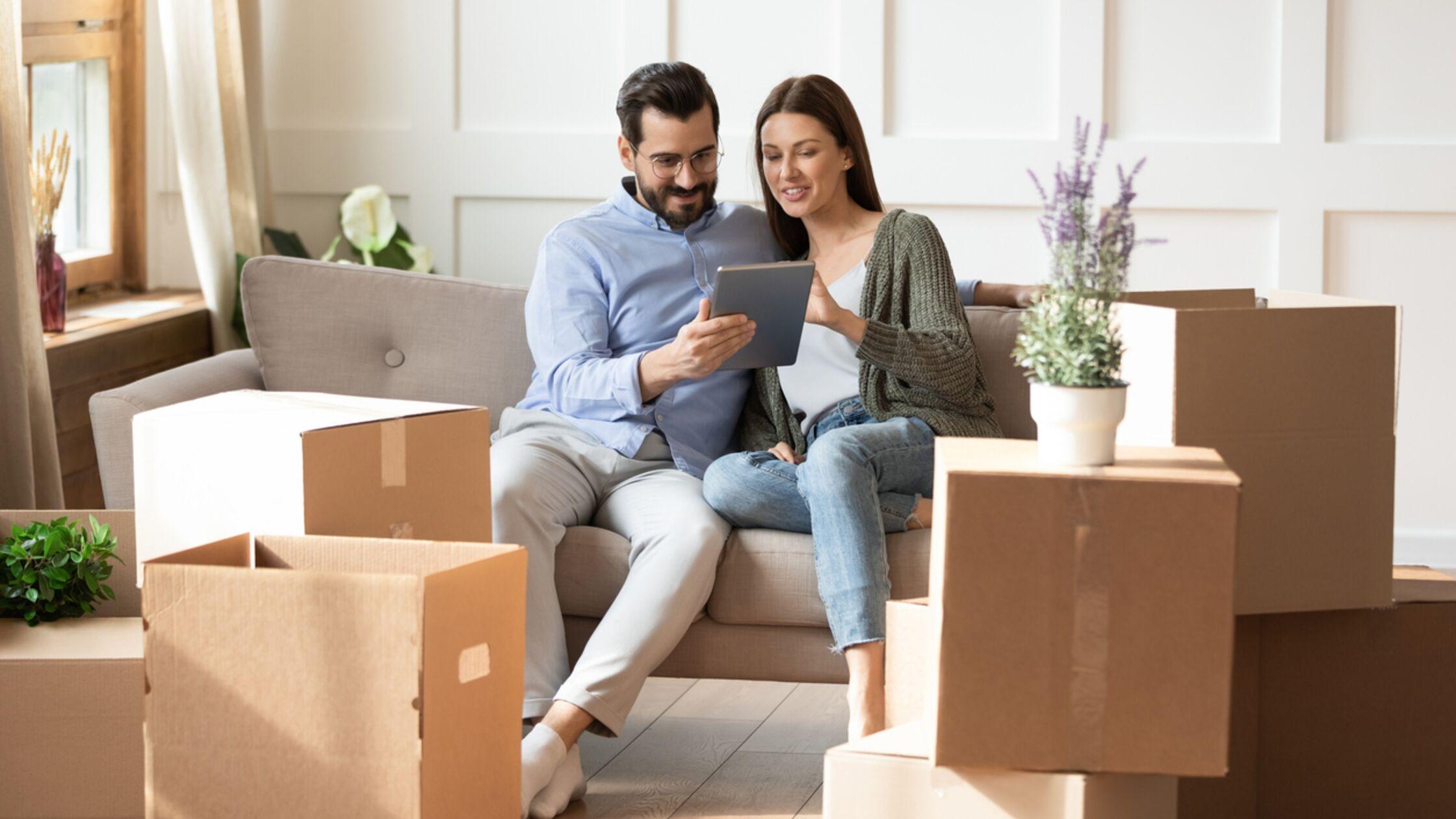 Junges Paar richtet Wohnung mit App ein
