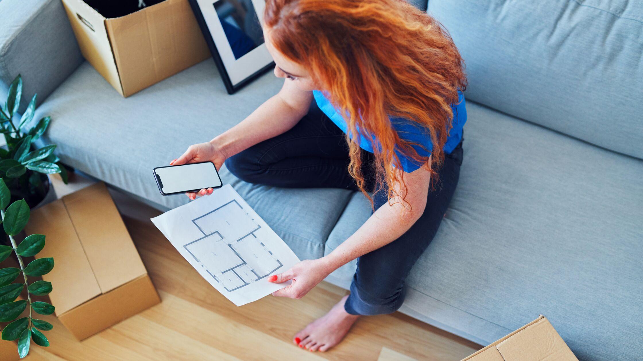 Frau richtet Wohnung mit App ein