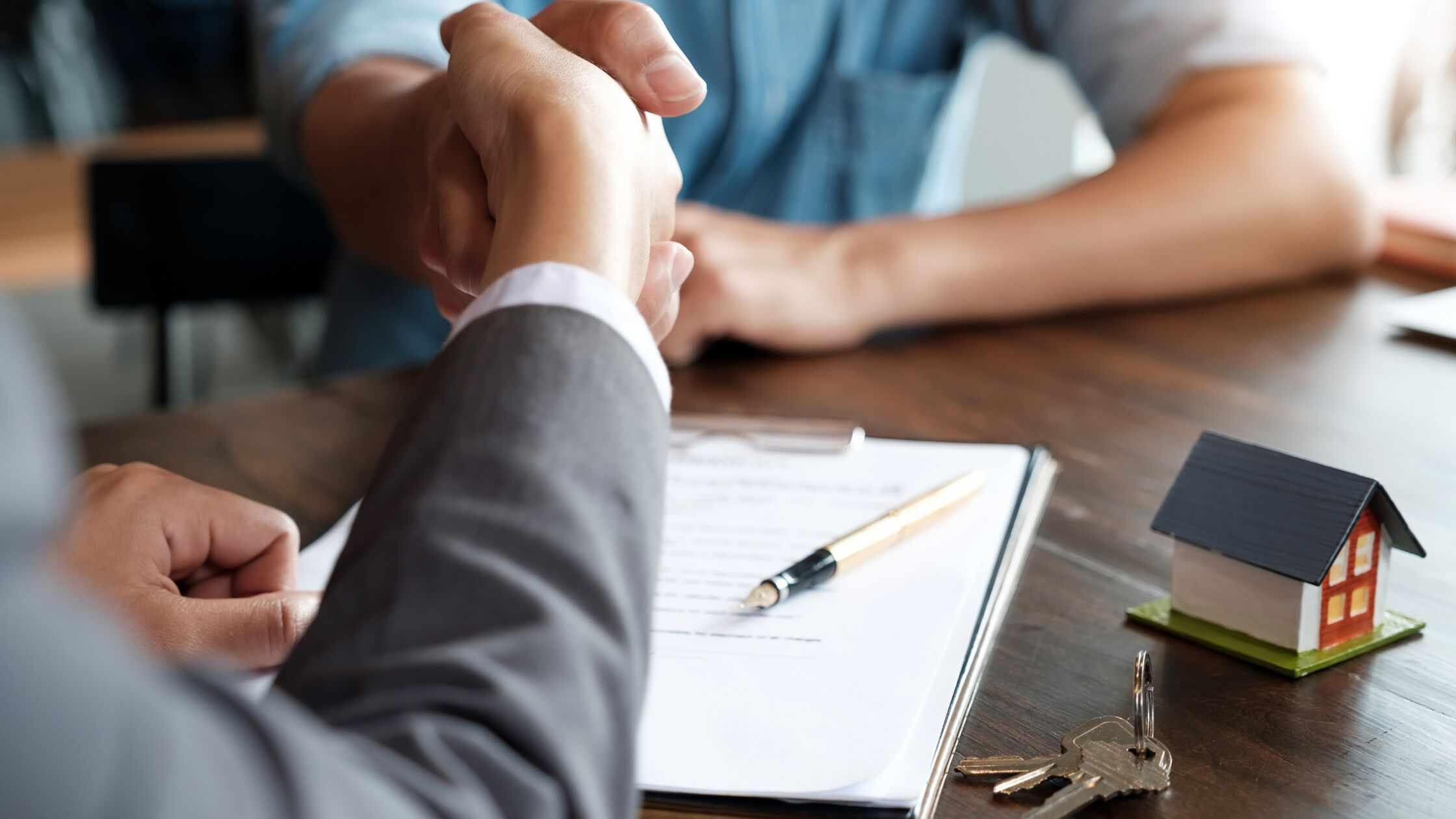 Personen besiegeln einen Vertrag mit Handschlag