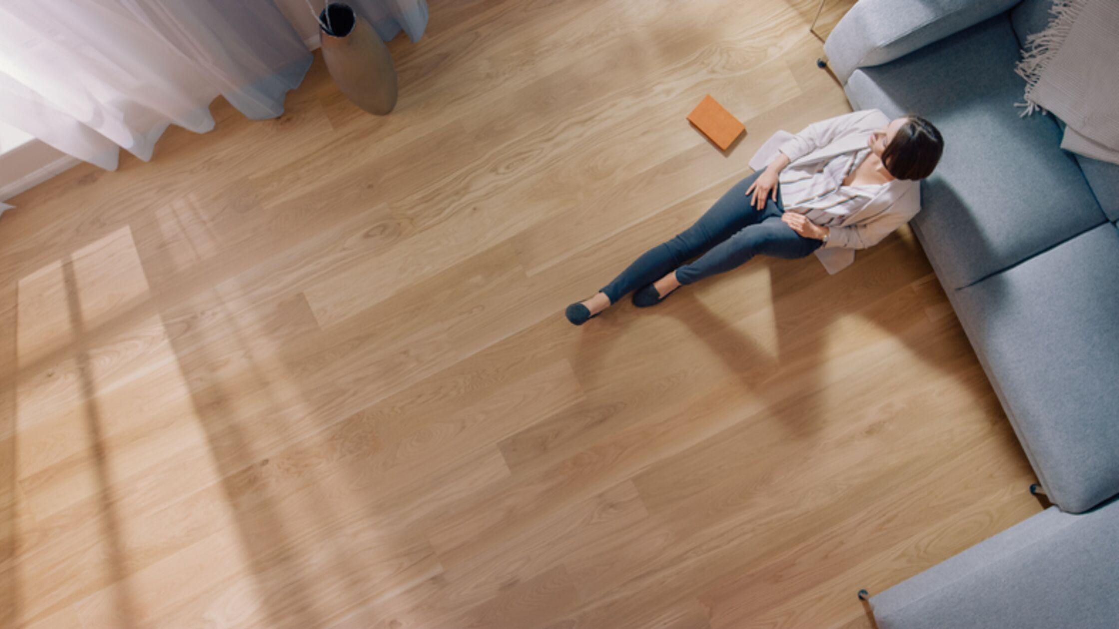 Frau sitzt auf Parkettboden