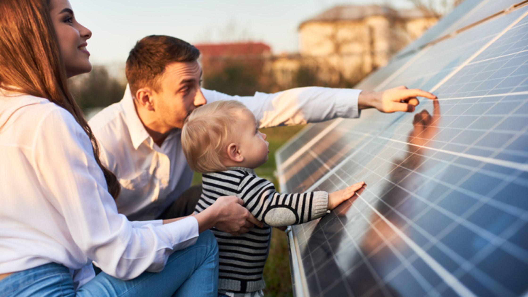 Junge Familie vor Solarpaneel