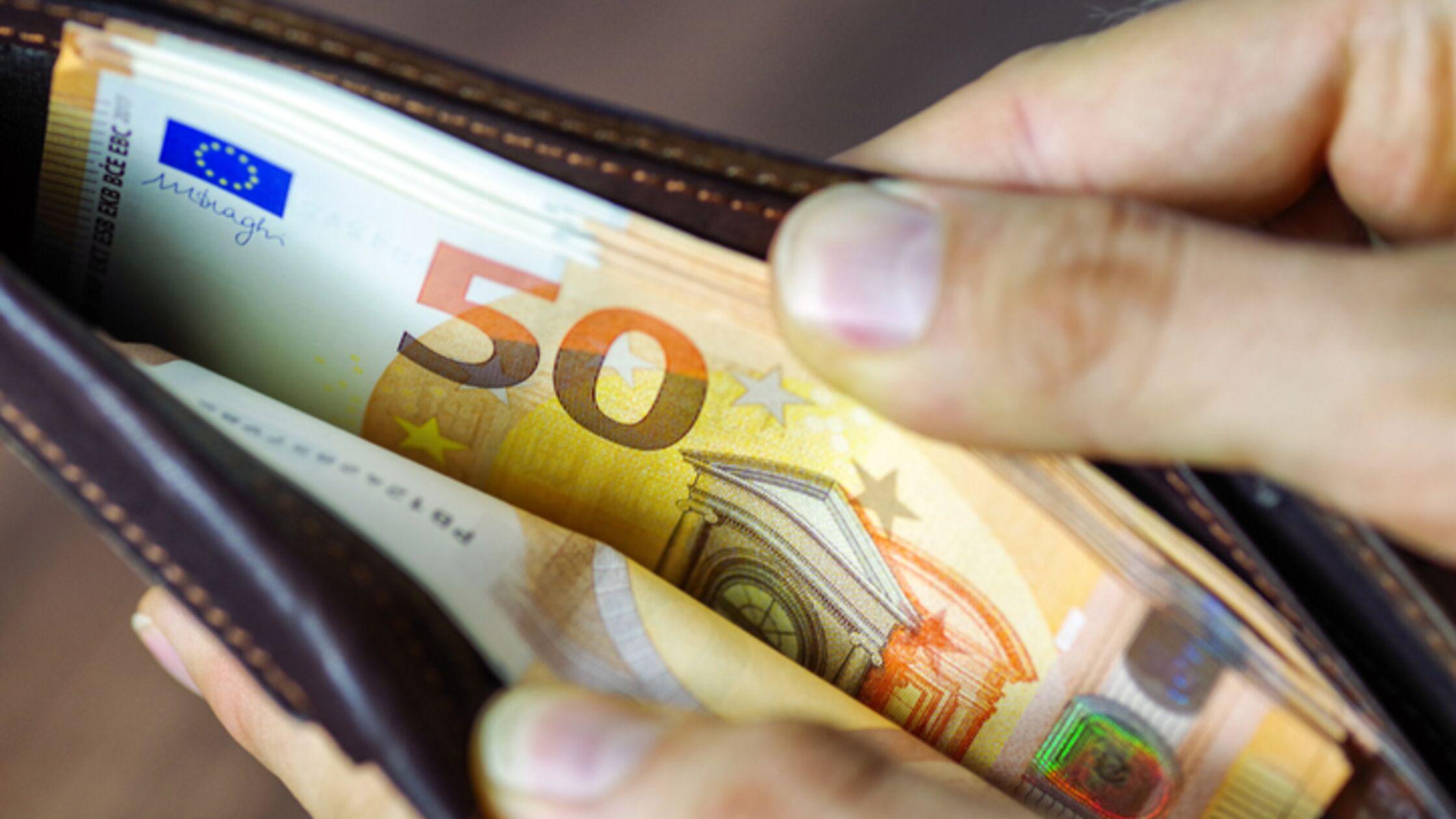Hand öffnet Portemonnaie mit Geldscheinen
