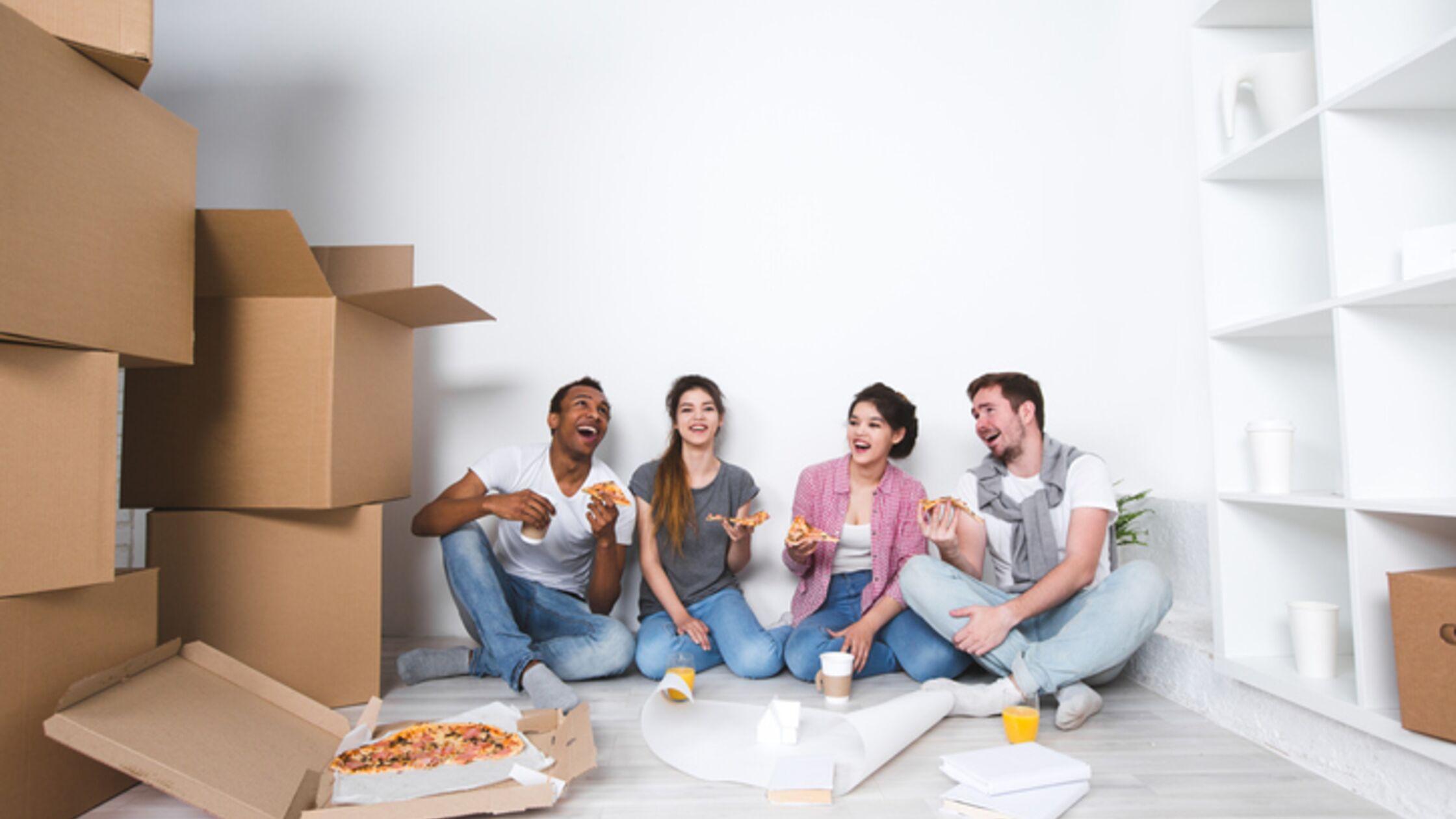 Umzugshelfer sitzen auf dem Boden und essen Pizza