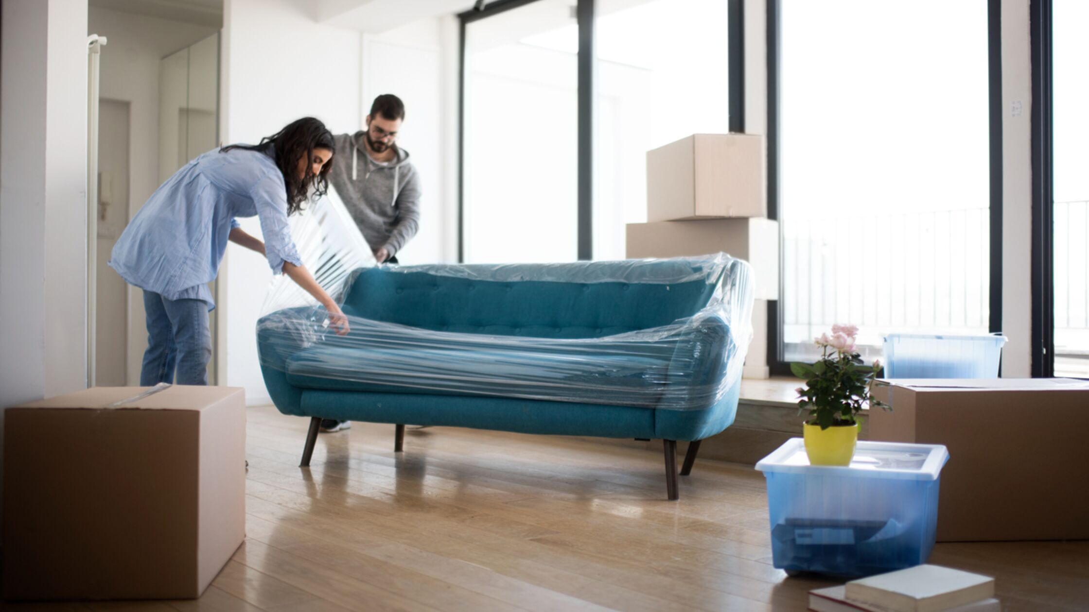 Paar wickelt Sofa in Stretchfolie