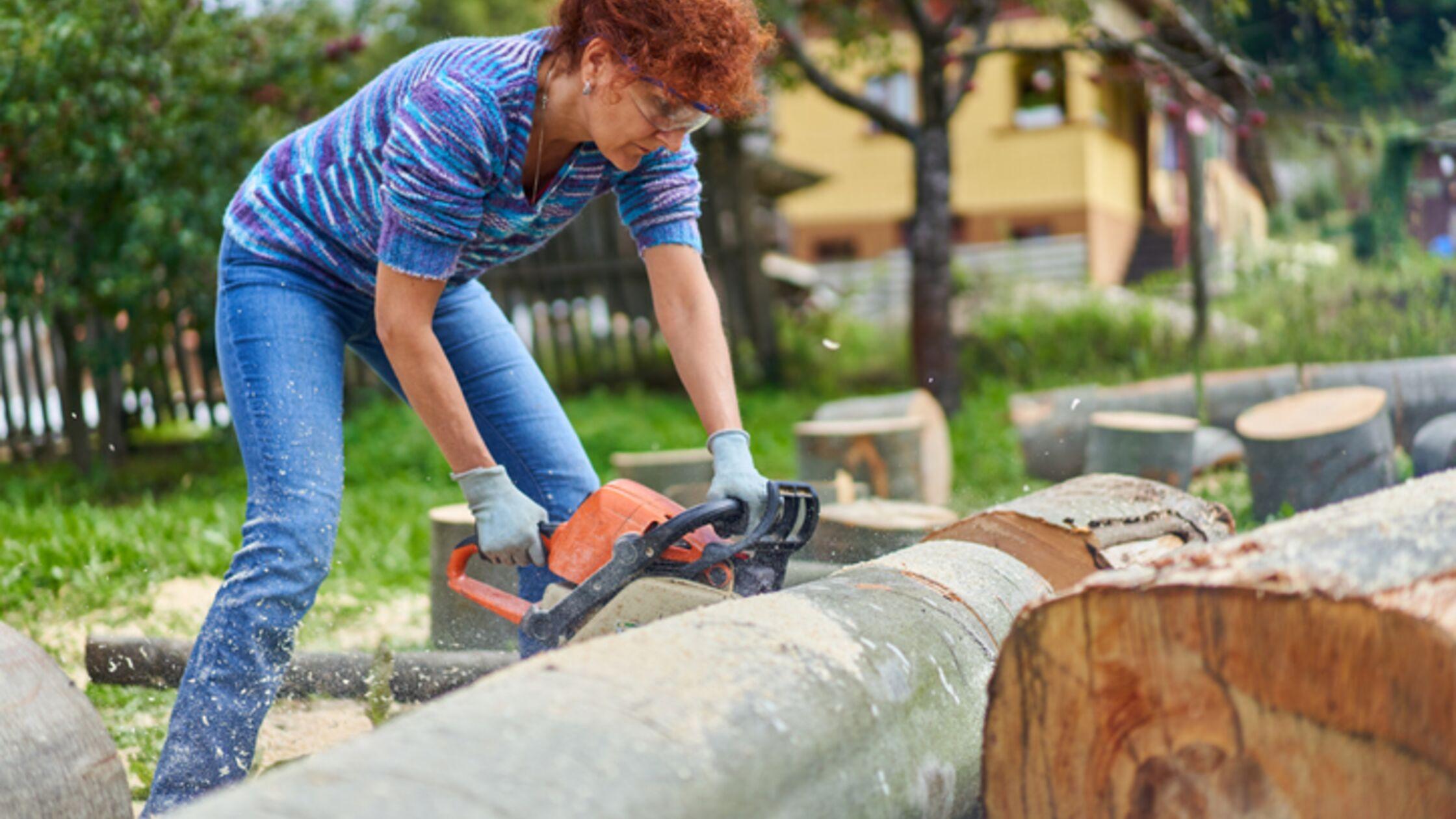 Frau fällt einen Baum mit Kettensäge