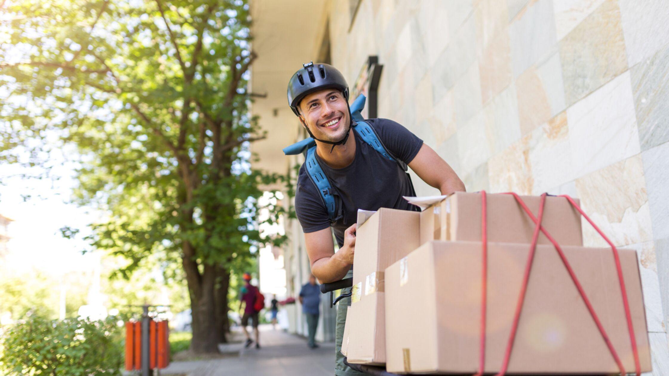 Mann auf Fahrrad, auf das Kartons geschnallt sind