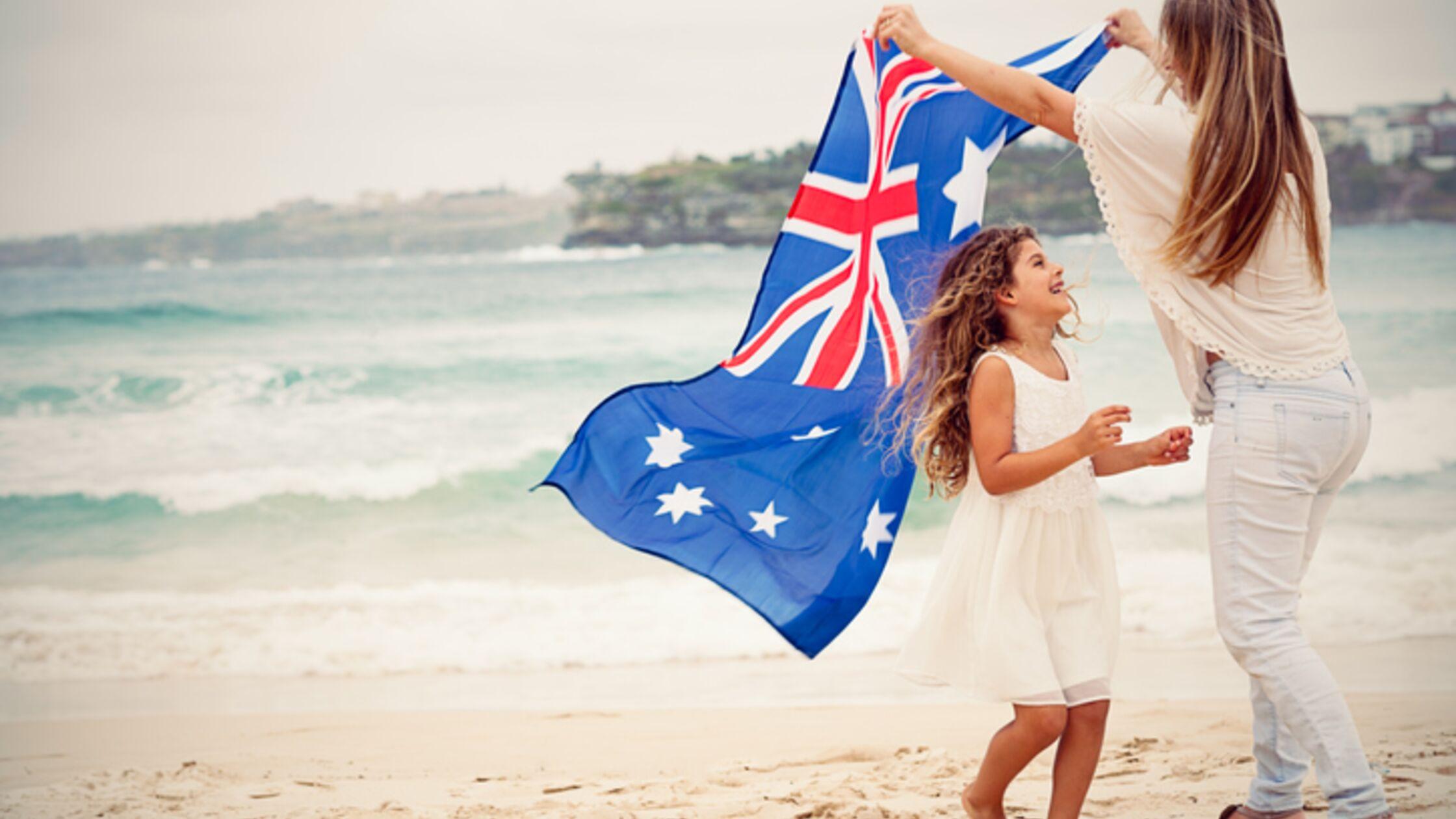 Frau und Tochter mit Australienflagge am Strand