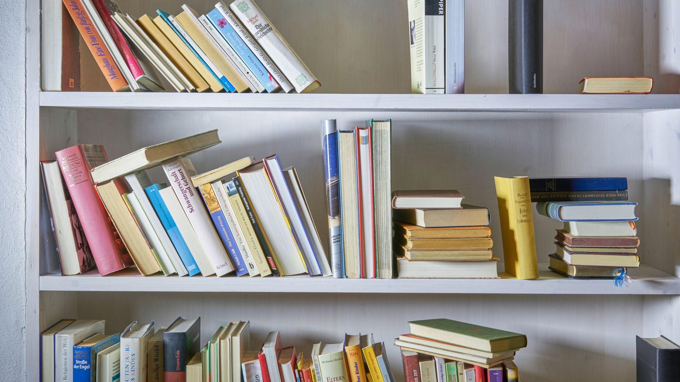 Bücher stehen schräg und durcheinander in einem Regal