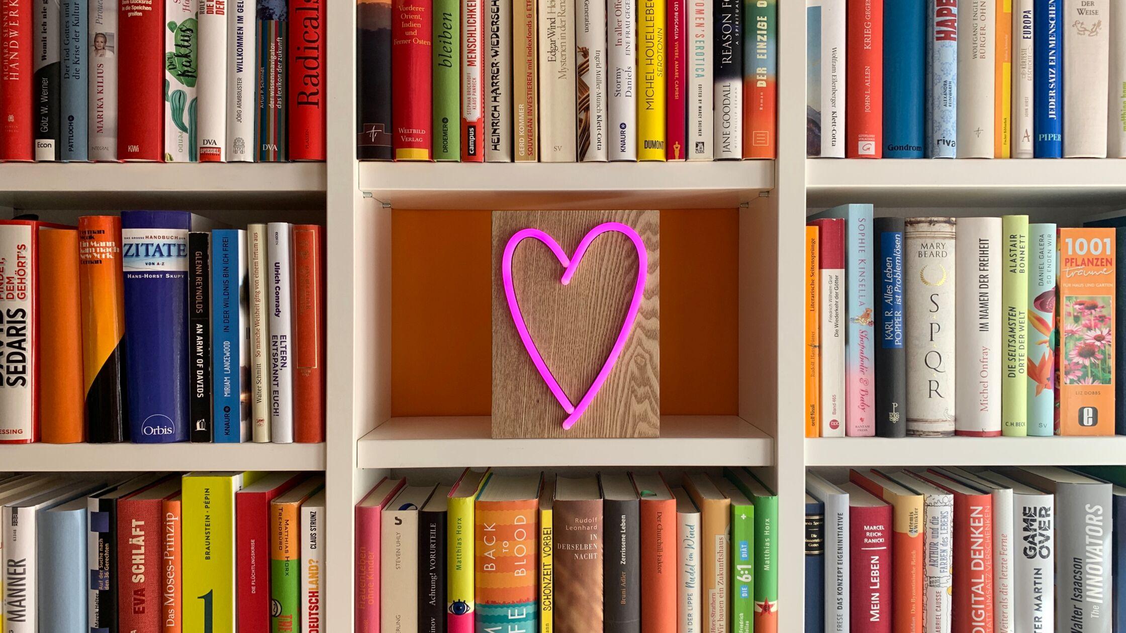 Bunte Bücher im Regal mit Neon-Herz in der Mitte